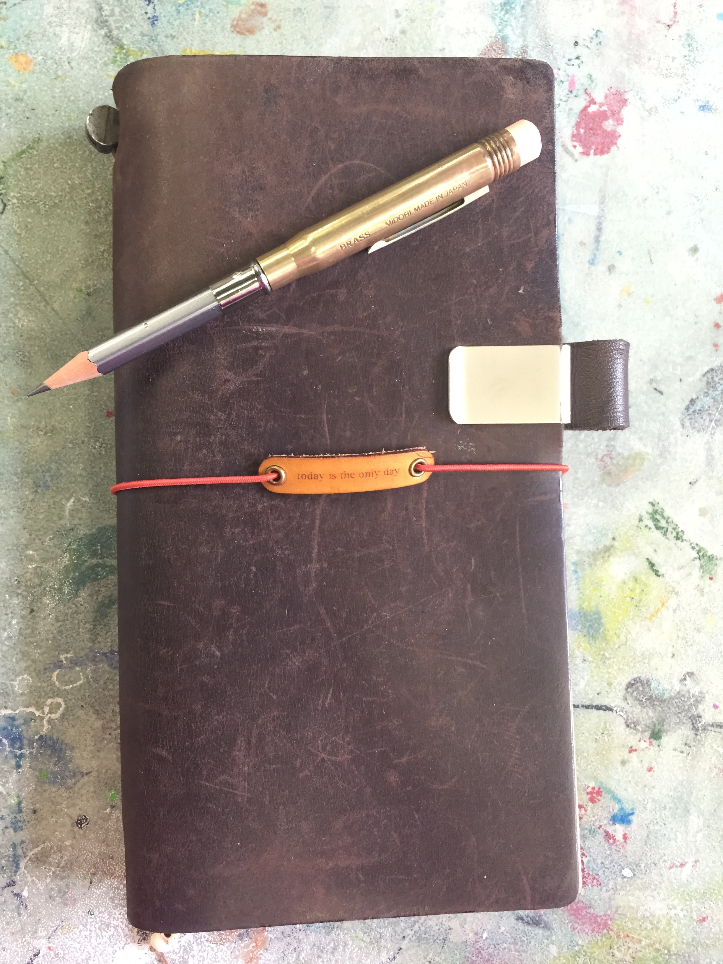 My Traveler's Notebook with my brass pencil and charm from  Baum-Kutchen.