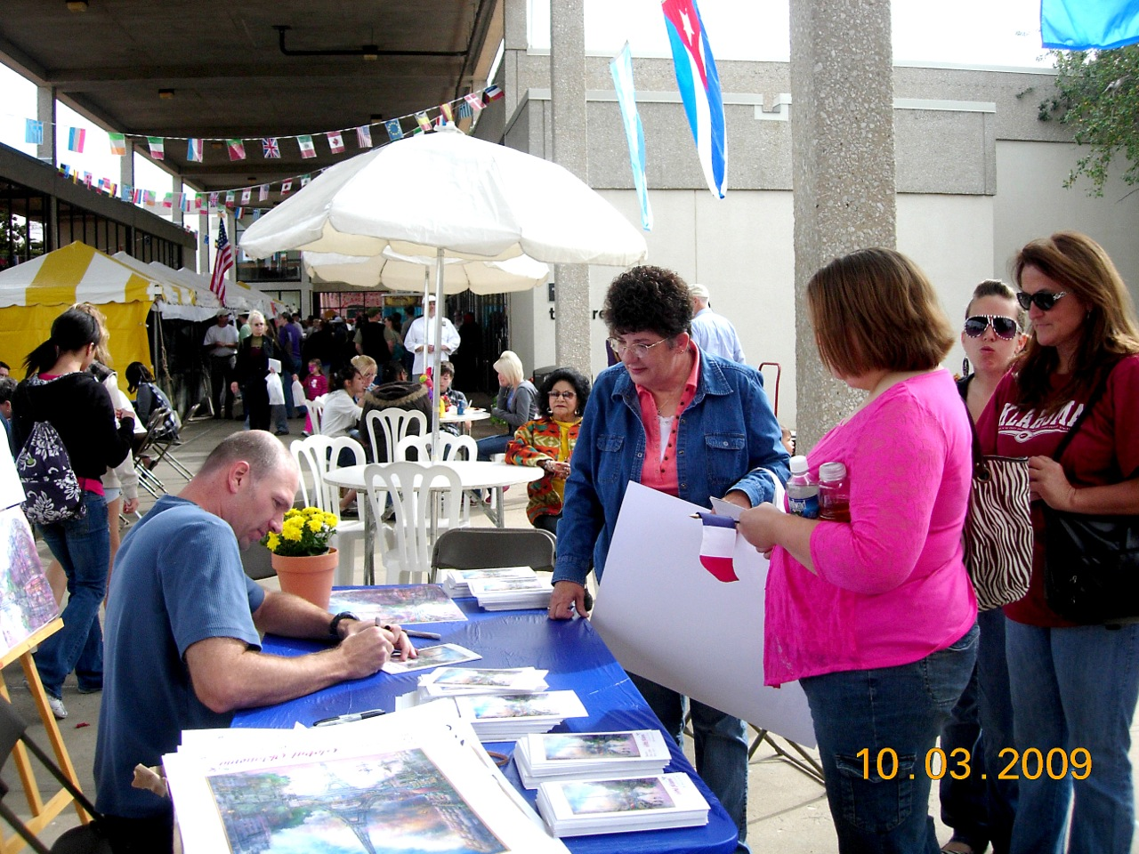 Jonathan signing posters at 2009 Global Oklahoma. Food Court in background.