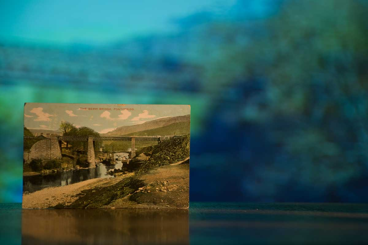 Postcard from 1905 showing theBerw railway bridge, near Pontypridd, Background video projection shows the now disused bridge