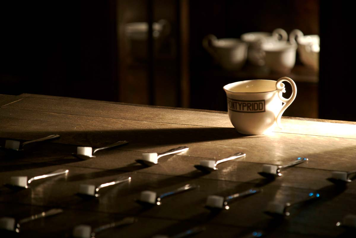 Fired bone china cup with decal depicting hand painted station sign. 60 spoons containing sugar lumps refering to dialogue from the film 'Brief Encounter'