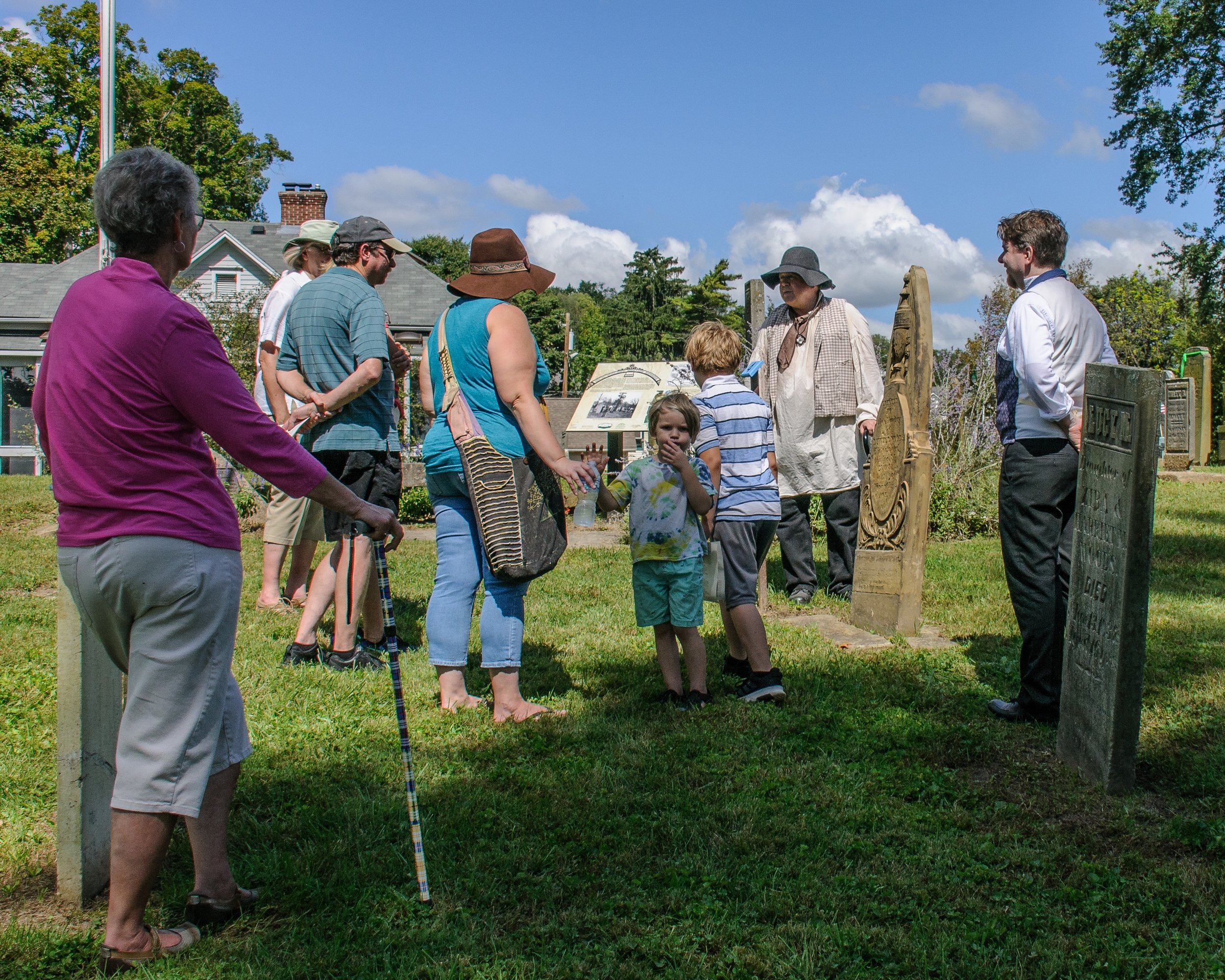Rev. Thomas Hughes (Brian Gregory) tells visitors about his stone-carving work on Luther Woods' headstone.