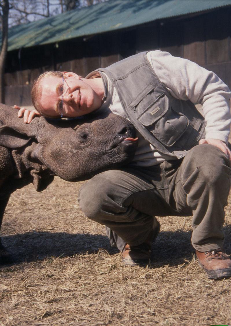 Wildlife Artist Eric Wilson with rhino at rhino sanctuary. Zimbabwe anti poaching rhino sanctuary.