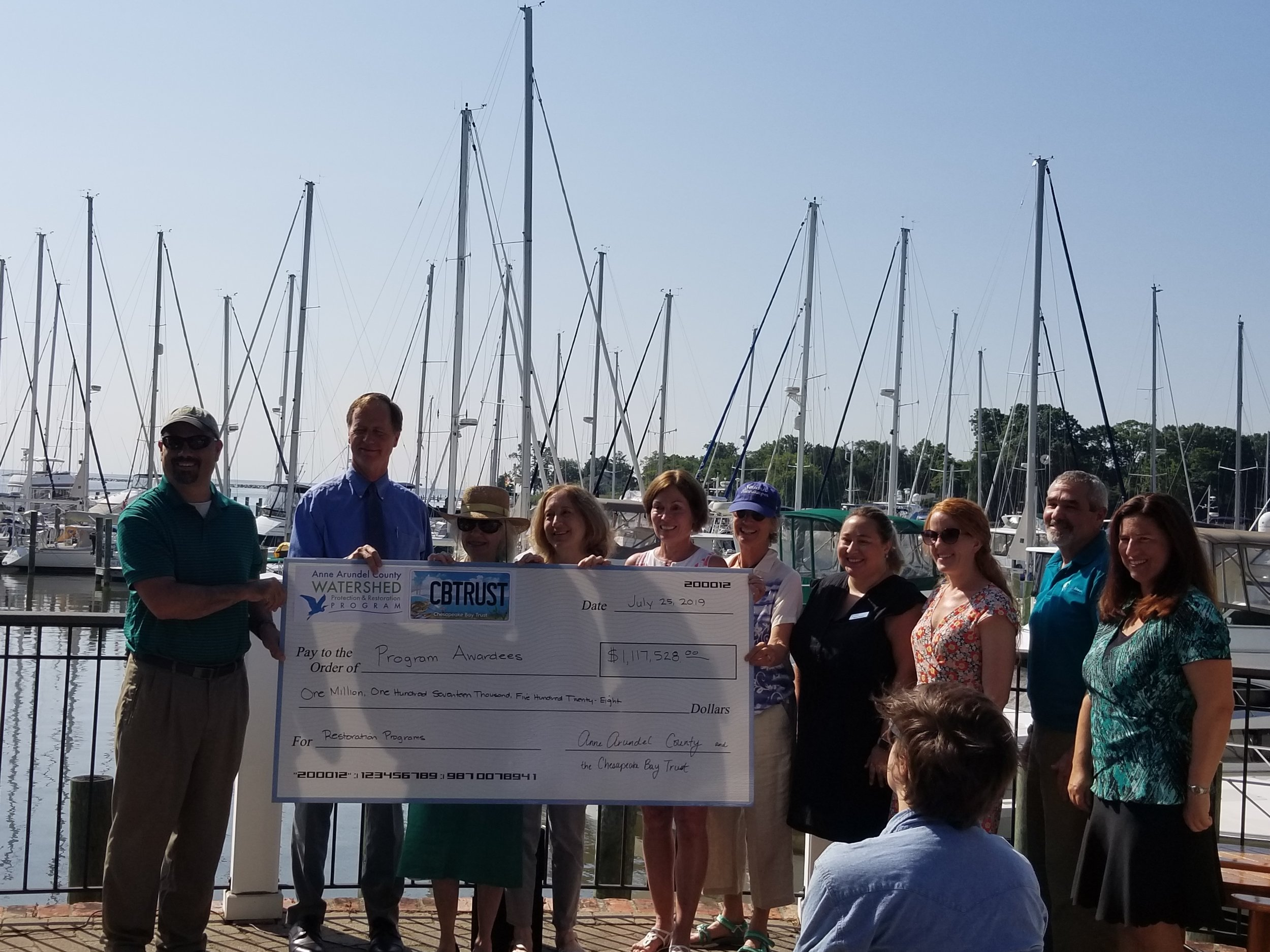 Severn Riverkeeper Sara Caldes and Winchester Community Leader Cathy Noon ceremonially accept funds from the Chesapeake Bay Trust and Anne Arundel County at a press event on Thursday. County Executive Steuart Pittman and Watershed Protection and Restoration Services Administrator Erik Michelsen join in holding the check along with three other grantees.