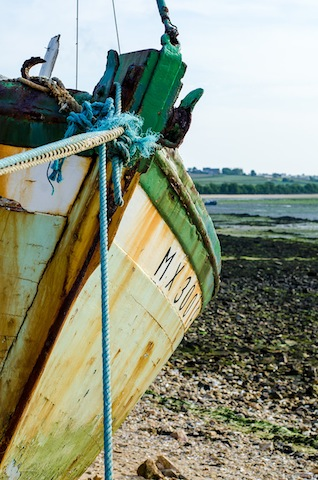 Fisherboat stranded on the shore. The boat will have to wait till the water reaches its highest level.