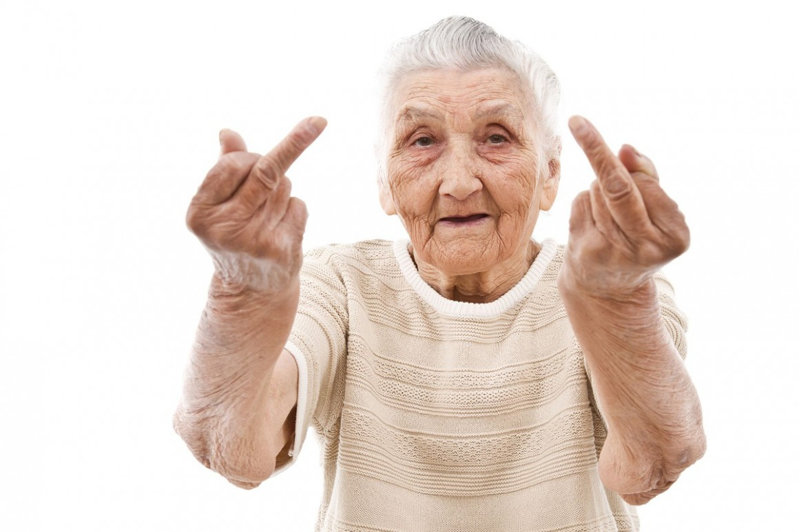 Image description: an elderly person giving the camera the middle finger with both fingers.