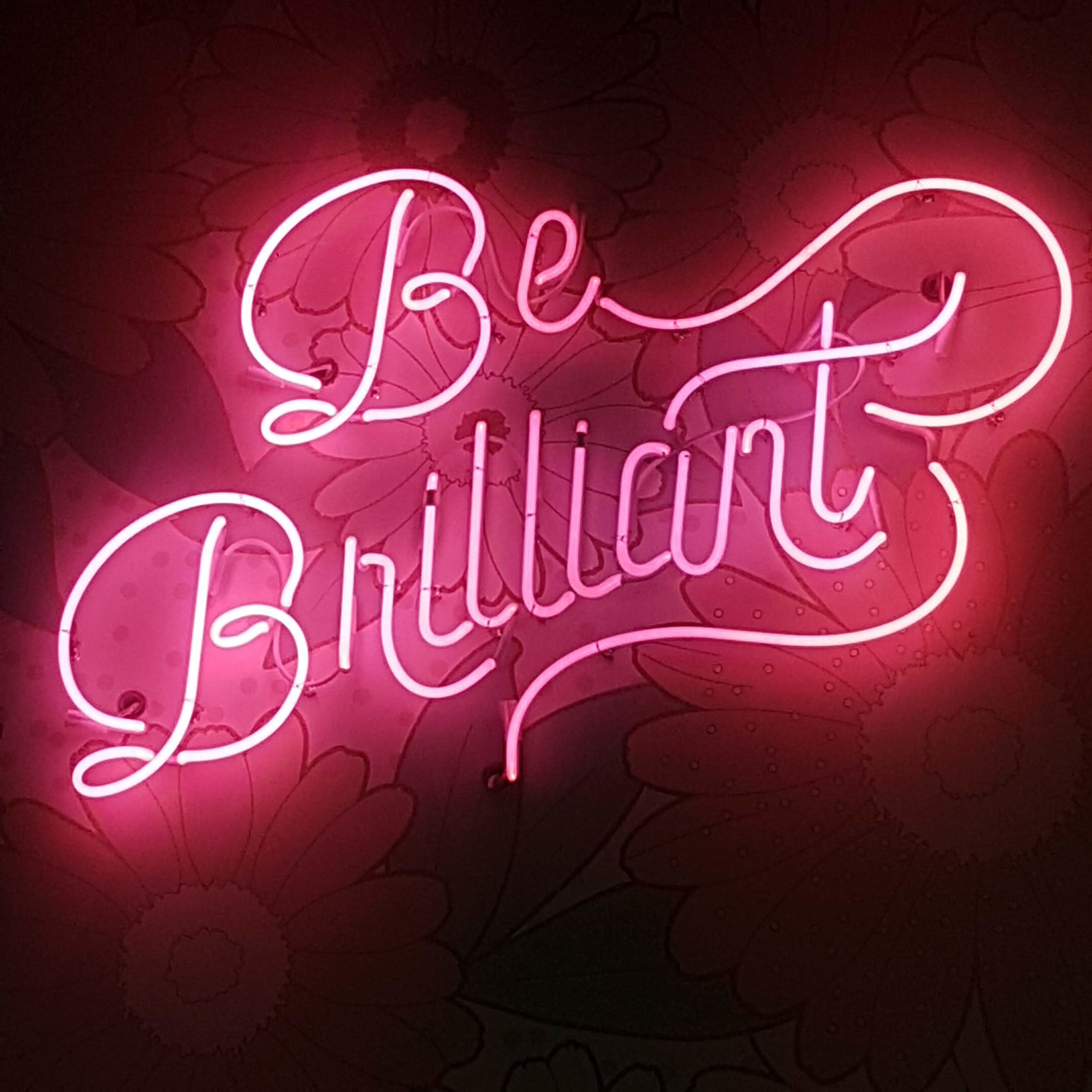 Image description: A neon pink sign that says BE BRILLIANT. Taken in Austin, TX.