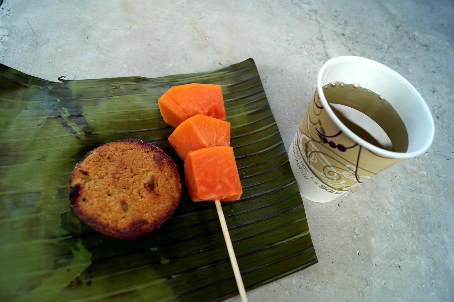 A mid-morning snack. They all looked like this: baked good (this time, rice/corn flour base and I think it was orange) and fresh fruit on a skewer (papaya, here) served on a fresh banana leaf with either coffee or a chilled herb + fruit infusion