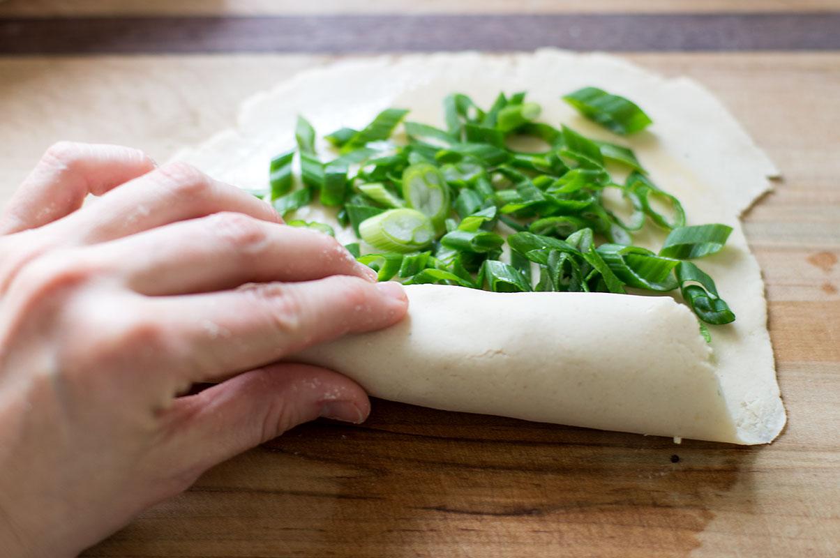 rolling up stuffed scallion pancake