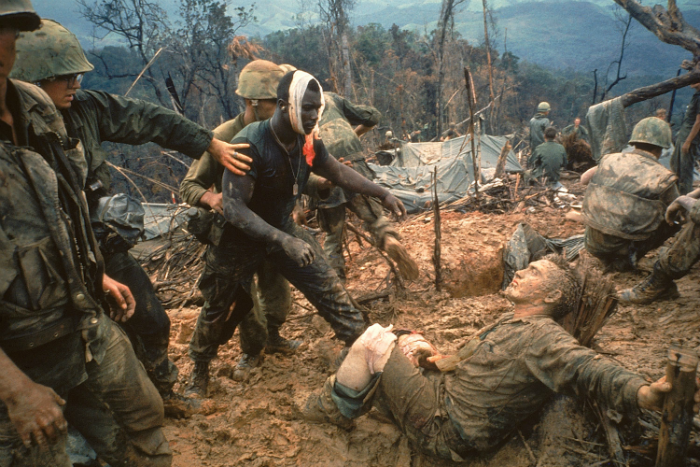 Reaching Out  (1966) by Larry Burrows Wounded Marine Gunnery Sergeant Jeremiah Purdie (centre) moves to try and comfort a stricken comrade, wounded for the third time, after a fierce firefight during the Vietnam War