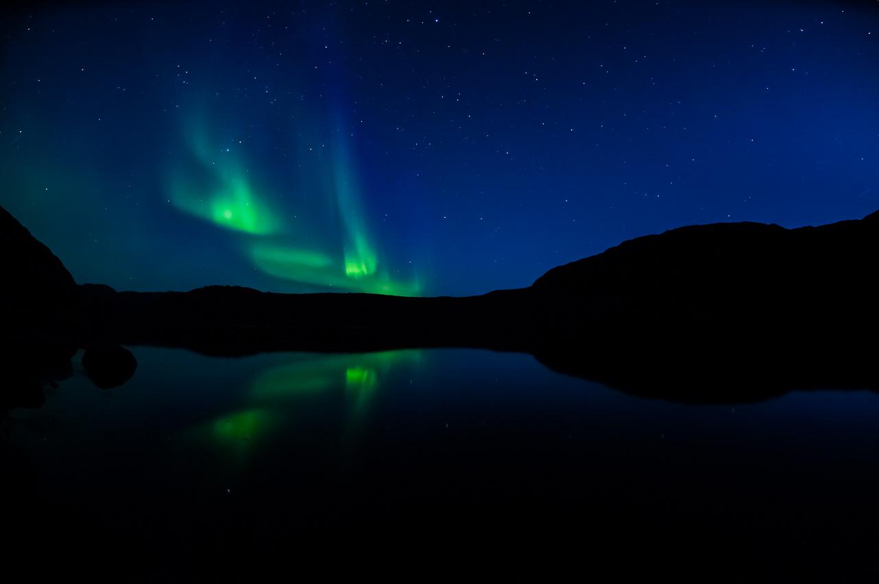 Polární záře nad jedním z drobných grónských jezer. Jezero, jak je zde obvyklé, nemá žádné jméno. Místní Inuité totiž věří, že jsou jména posvátná a mají duši, která pochází z polární záře. Pokud by jména byla používána zbytečně, mohla by polární záře vyhasnout.
