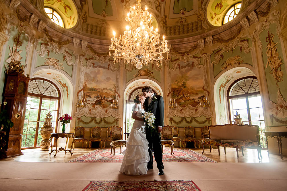 Evička & Tomáš, 11. srpna 2012, Vizovice  Lepší místo na svatební portrét jsem ještě nikdy nenašel. Kombinace tří světel (blesky, lustr a denní světlo), na fotografování byly zhruba tři minuty. TECHNIKA : Nikon D300, Nikon 12−24 mm f/4 G IF-ED AF-S DX Zoom-Nikkor (@12), 1/40 s, f/4, ISO 400, Metz 48 AF-1, Nikon SB-900, PocketWizard MiniTT1 & FlexTT5