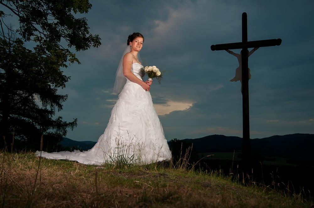 """Jana & Michal, 11. června 2011, Křížový vrch u Rynartic  """" Michale, tváříš se u toho jak ropný magnát. Neumíš nějaký normální výraz? """" zeptal jsem se kamaráda, kterému jsem svatbu s velkou pýchou odsvědčil a fotil zároveň. """" Hele, tak si Janu vyfoť samotnou… """" """" Tak jo! """" řekli jsme jednohlasně Jana i já… Dva blesky, tehdy ovládané ještě v infrakanálu. TECHNIKA : Nikon D300, Nikon 12−24 mm f/4 G IF-ED AF-S DX Zoom-Nikkor (@20), 1/125 s, f/5, ISO 320, Metz 48 AF-1, Nikon SB-900"""