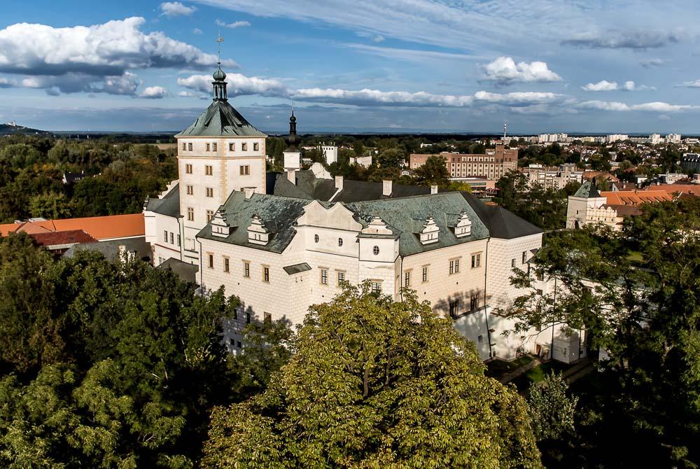 """Na tomto místě stál původně vodní hrad, tedy od třináctého století. Dnes se jedná o renesanční zámek, který na pomezí patnáctého a šestnáctého století patřil věhlasnému rodu Pernštejnů. Přestože v něm rod sídlil jen krátce (69 let), za Viléma z Pernštejna došlo k silné fortifikaci (výstavbě opevnění), která se zachovala dodnes. Synové Viléma Pernštejna Vojtěch a Jan pak výrazně přispěli k renesančním úpravám zámku.  Tento záběr byla velká sázka do loterie − stál jsem totiž za stromy, odkud bylo možno bezpečně vzlétnout a přistát. Co """"vidí"""" vrtulník, jsem si tak skutečně mohl jen představovat. Dopadlo to nicméně na první dobrou.  TECHNIKA: Nikon 1 J1, Nikkor 1 10 mm f/2,8, 1/1000 s, f/6,3, ISO 100, korekce expozice −1,7 EV, 27. září 2013"""