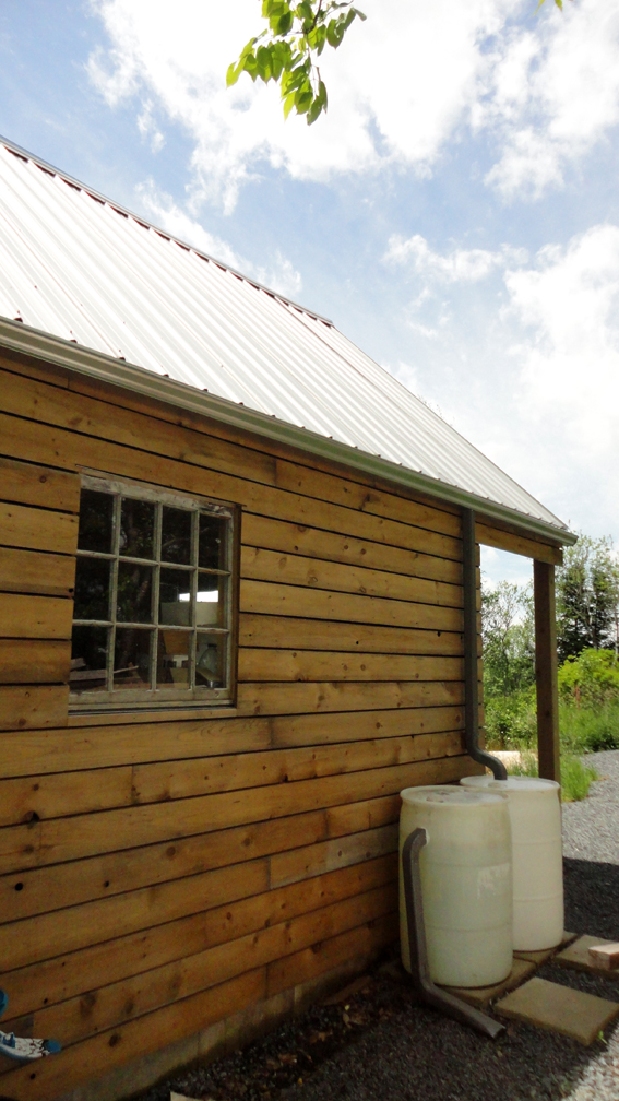 The shed used salvaged windows and is used to collect rain water.