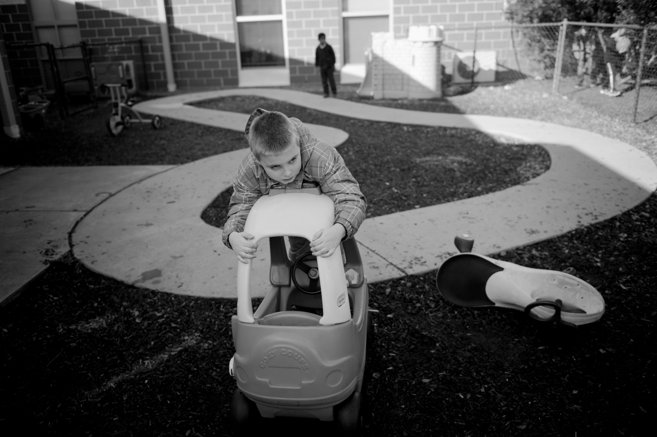 Marcus O'Loughlin looks past his fenced in play area, designated for children with autism, to the children outside. This is an outtake from the story World Within Our Own