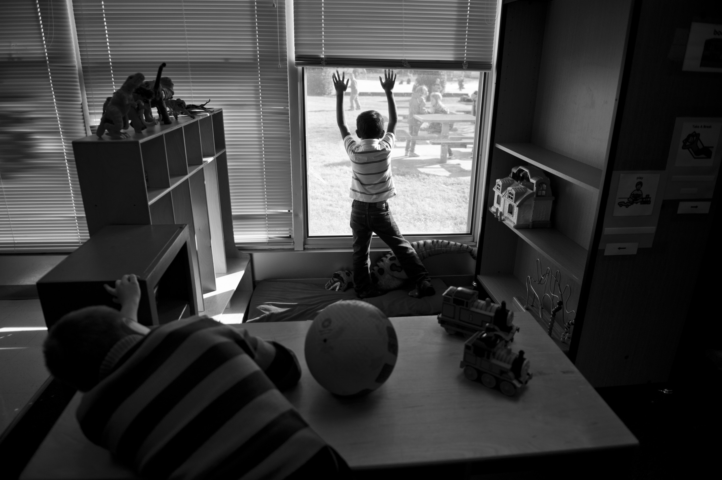 Marcus and a classmate in his autism-specific classroom long to be outside playing with the others.