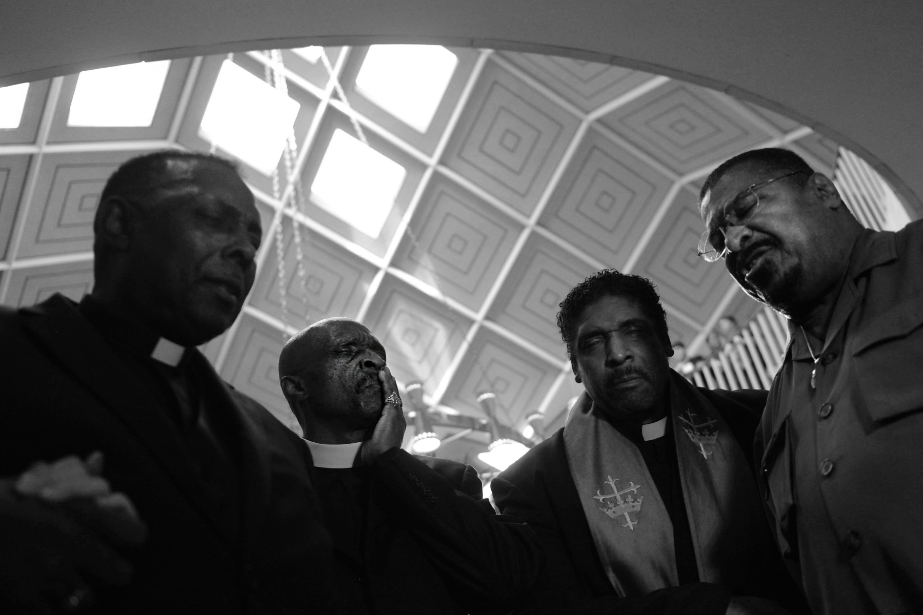 Leaders of the N.C. NAACP pray outside the golden doors of the N.C. House of Representatives Chambers.