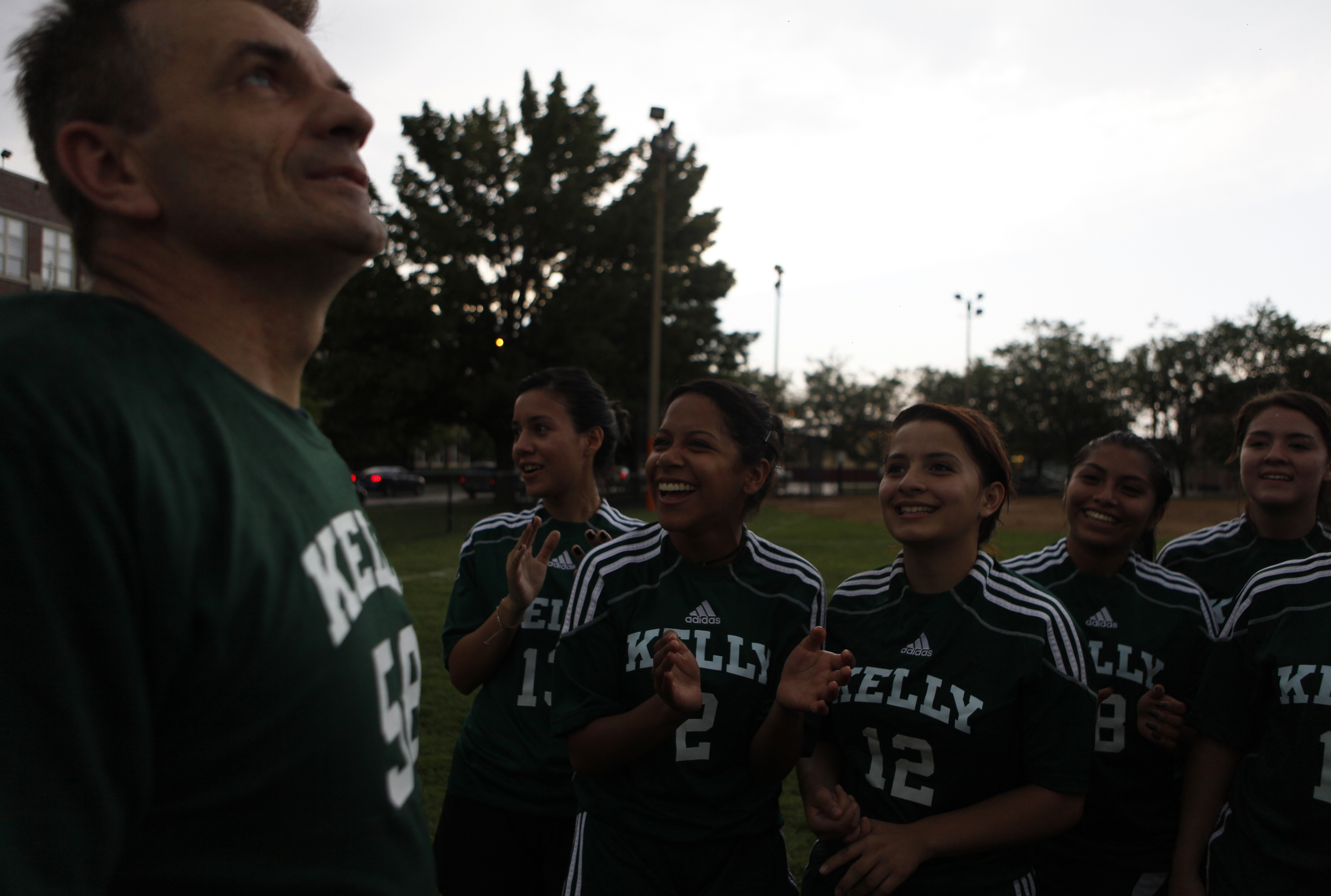Head Coach Stan Mietus looks up at the stormy sky as the girls chant during practice in front of the Kelly High School in Chicago on Tuesday, June 11, 2013. They were counting the number of seconds after a thunder clap to see if there was going to be lightning since they did not want practice to end. The Kelly High School girls varsity soccer team is almost entirely first-generation Hispanic Americans. Many of the girls struggle to convince their parents to allow them to play soccer.