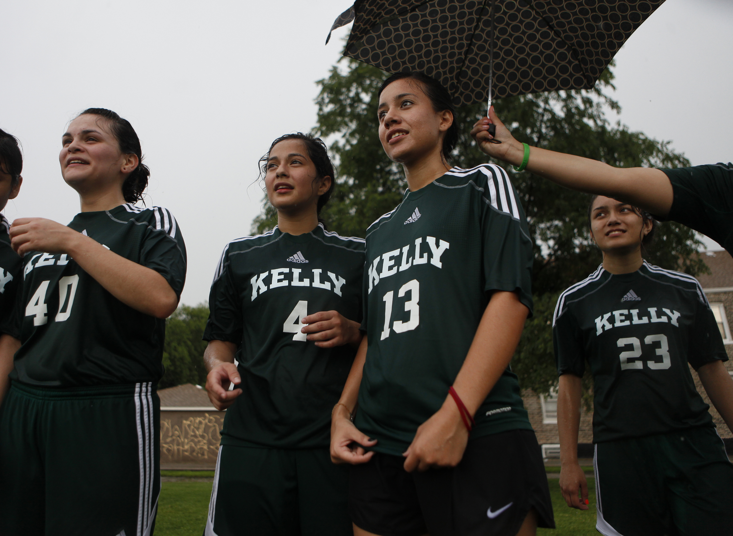 Cynthia Lucio, a junior, holds an umbrella out over Edith Garcia and Ana Flores' heads during practice in front of the Kelly High School in Chicago on Tuesday, June 11, 2013. The Kelly High School girls varsity soccer team is almost entirely first-generation Hispanic Americans. Many of the girls struggle to convince their parents to allow them to play soccer.