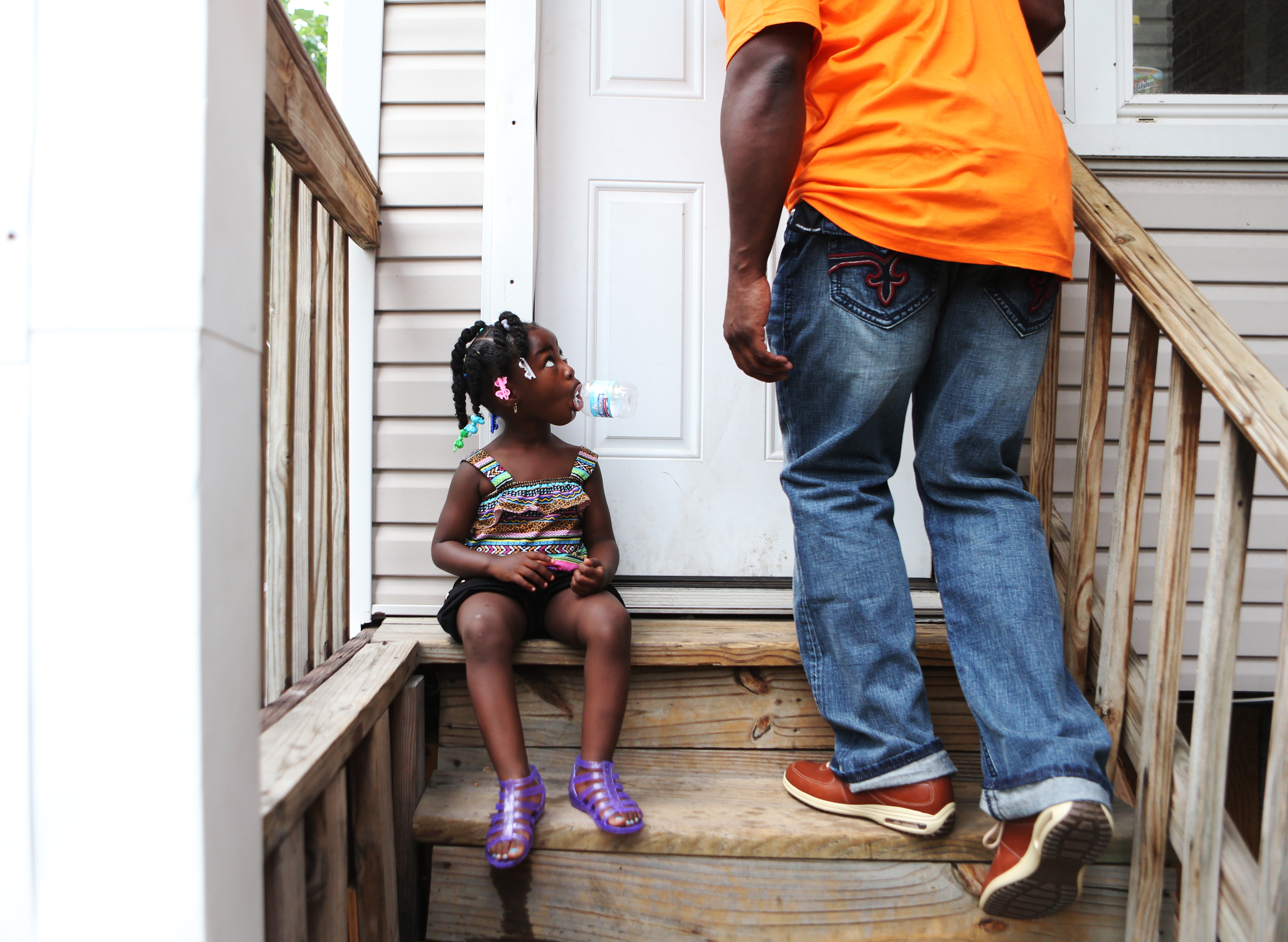 One of Daniel's many nieces, Kay-Kay Davis, 2, looks up at him as he passes into his Aunt Marie's house on Thursday, July 4, 2013. She was born while Daniel was incarcerated, so she does not know that he is her uncle.
