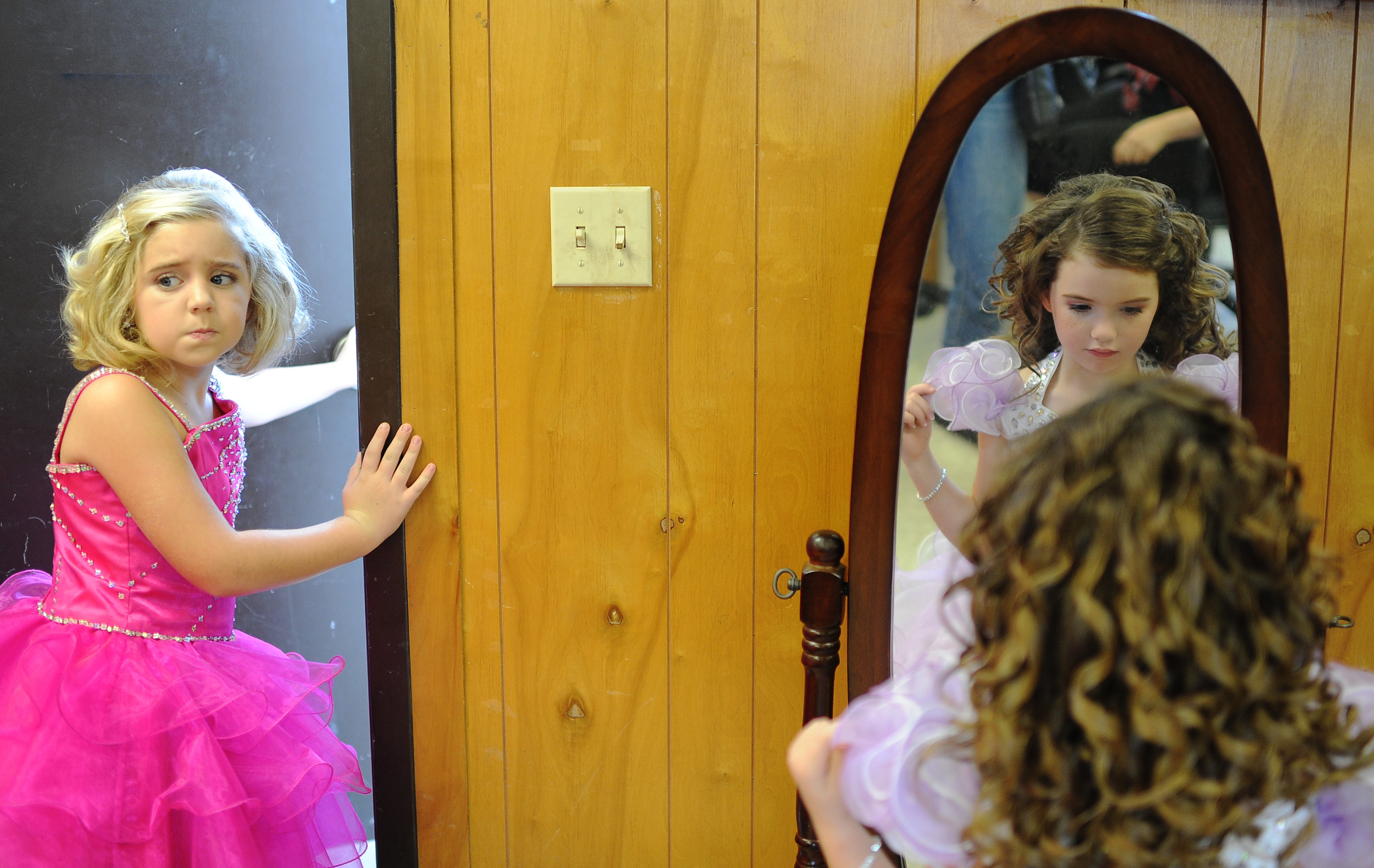 """Carlie Braglin, 8, left, looks back at her fellow competitors before heading out the door to compete in the 6-8 years division of the Harvest Pageant for Babies and Children at the 20th annual Hillsborough County Fair in Brandon on Sunday, October 20, 2013. Meanwhile, Isabelle Murphy, 5, right, checks her make-up and straightens her dress in the mirror prior to competing in the 4-5 years division. The children were divided into groups by age and gender for the competition. Each child, often with the help of his or her mother or father, walked up on the stage to be judged. Many of the girls shyly waved and blew kisses to the crowd. The beauty pageant cost up to $70 to register for all of the events, which included """"most photogenic,"""" """"prettiest eyes,"""" """"best smile,"""" and """"best attire."""" The judging was based on facial beauty, overall appearance, and personality on stage, but every entrant received a participation award."""
