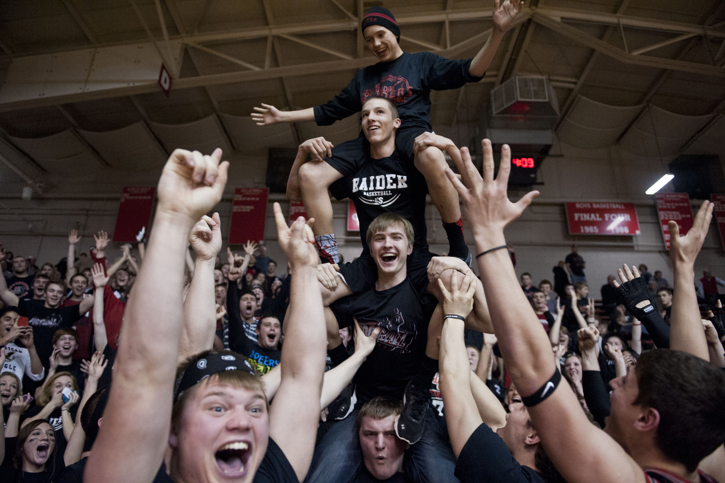 Southridge senior Ethan Schwoeppe, bottom, Luke Stetter, junior, Drew Dearing, freshman, and Braden Harding, freshman, stacked on top of each other and cheered for the Raiders during halftime of their game against Washington in the IHSAA Class 3A sectional tournament in Huntingburg, IN on Wednesday.  The Raiders lost 41-35.