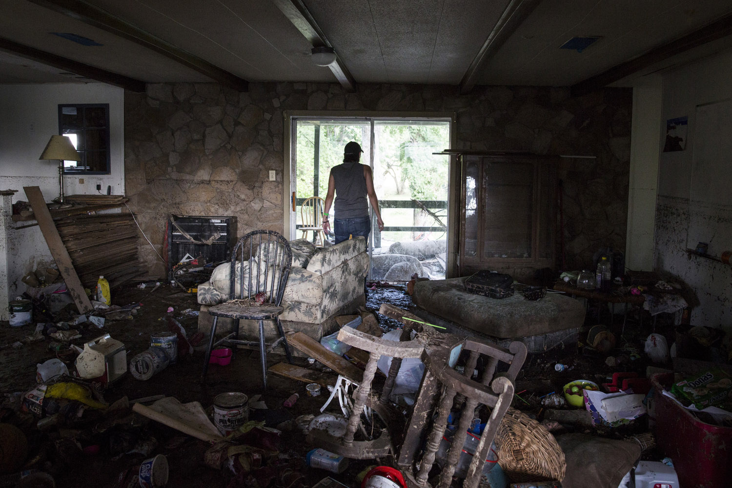 "Glenda Bamberger looks out of the back door of her home in Blanco, Texas on Friday, May 29, 2015. Bamberger, who was born and raised in Blanco, said, ""We put everything into buying this house and now I am not sure we will want to rebuild.""  The line on the wall to Glenda's left shows how high the water rose."