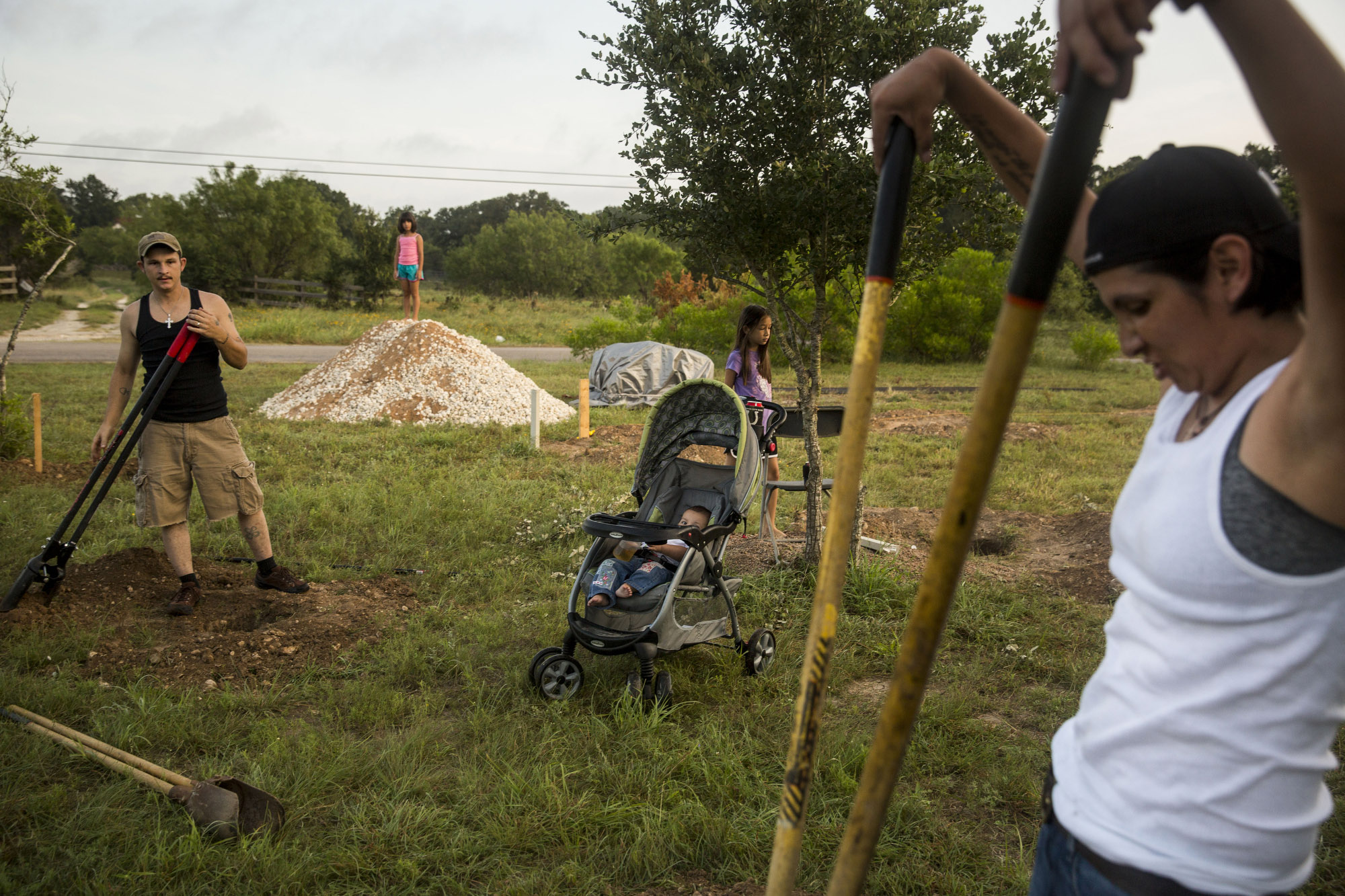 Glenda Bamberger, right, and her husband Jarrell Bamberger, left, widen holes dug in their yard in Blanco, Texas on July 11, 2015.  Their home was destroyed in the floods that occurred in May along the Blanco River in Central Texas.  They poured a concrete pillar in each of the twelve holes for the house they are building to replace the one that flooded.  The house will be eight feet off the ground in the hope that it will not be affected by future floods on their property.