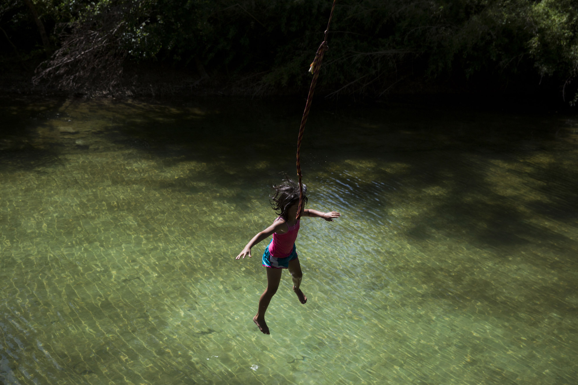 "Serenity Bamberger, 7, falls from a rope swing behind her house into the Little Blanco River on July 11, 2015 in Blanco, Texas.  Two months prior, the same river flooded their home destroying the majority of the family's belongings.  Despite the toll the river has taken, Bertha Rivera, Bamberger's grandmother, said, ""The river bed was dry for years, so now that the water is here I tell the girls to take advantage of it all that they can."""