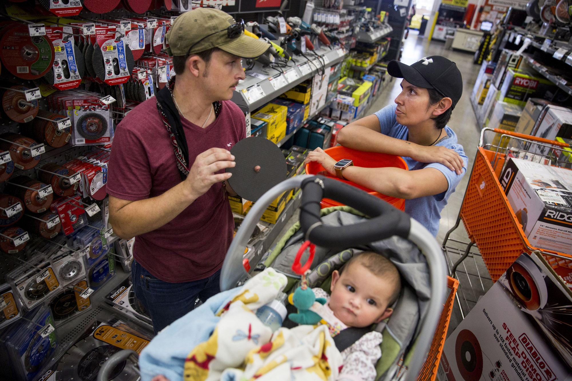 Jarrell Bamberger talks to his wife Glenda Bamberger about what they need to start building their home while their daughter Esmebella, 9 months, sits in their shopping cart at Home Depot in Bulverde, Texas on July 10, 2015.  They began construction on their new home the next day.