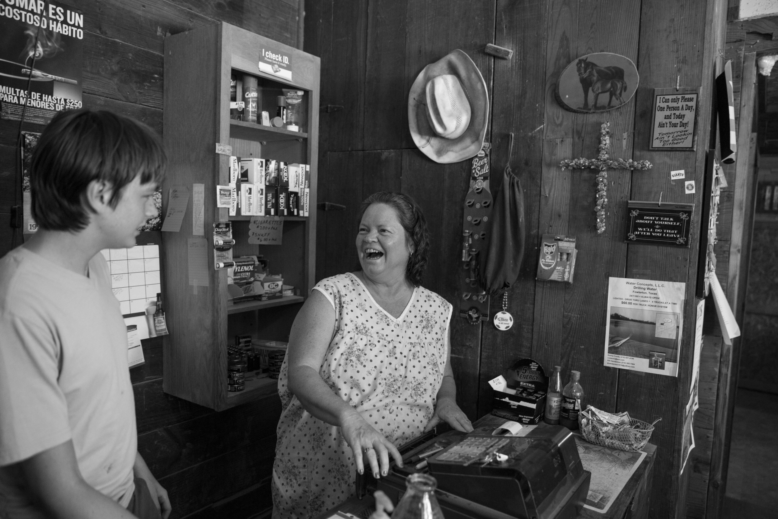 Joy Tipton and her son Evan Tipton laugh as they joke about how much Evan works at the Tipton family's roadside store The Little White House in Fowlerton, Texas on August 5, 2015.  The store is along the highway between Tipton, Texas and Cotulla, Texas, and mainly serves hunters and oil field workers.  Joy Tipton said that she hears fewer oil field trucks driving by everyday and that business is dwindling.