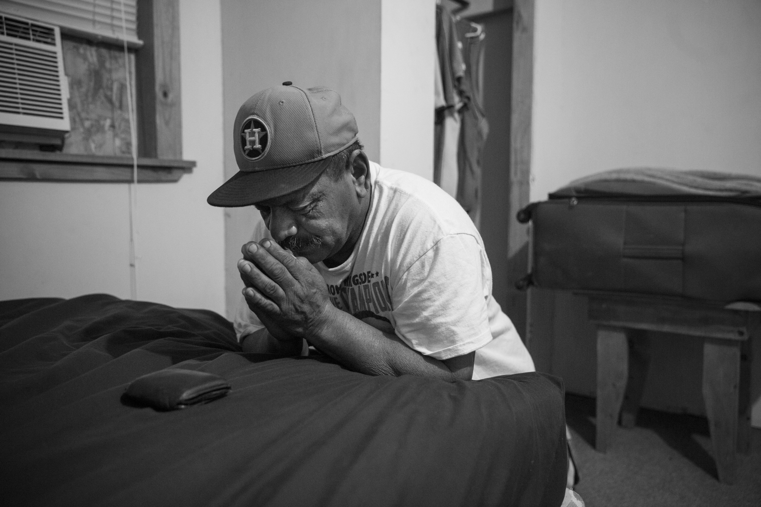 "Before dawn Tino Gaona prays in his bedroom on the morning of his youngest daughter's 24th birthday, which he is missing, in Cotulla, Texas on August 6, 2015.  ""I miss a lot of birthdays and holidays, but that is how it goes,"" he said. He prays every morning before going to work in the oil field.  After 20 years in the oil field, he considers it very dangerous work. Of God, he said, ""He's the reason I am still here, so I pray for everybody on my crew."""