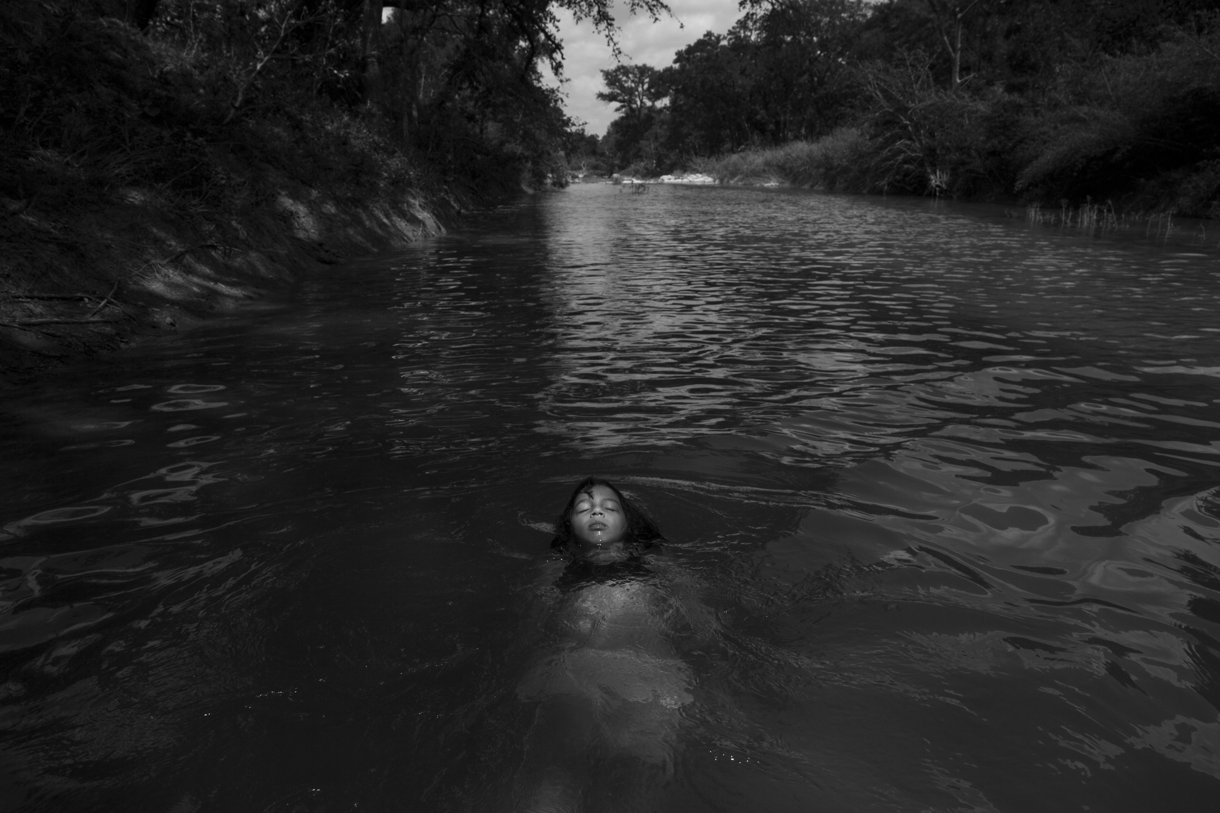 "Serenity Bamberger floats in the Little Blanco River along her family's property on August 18, 2015 in Blanco, Texas. Three months prior, over Memorial Day, the same river flooded their home and business destroying the majority of the family's belongings and source of income. The Memorial Day weekend flooding, which affected Texas and Oklahoma, killed 24 people according to The Associated Press. Three of those deaths occurred along the Blanco River of which the Little Blanco River is a direct tributary. Despite the toll the river has taken, Bertha Rivera, Serenity's grandmother, said, ""The river bed was dry for years, so now that the water is here I tell the girls to take advantage of it all that they can."""