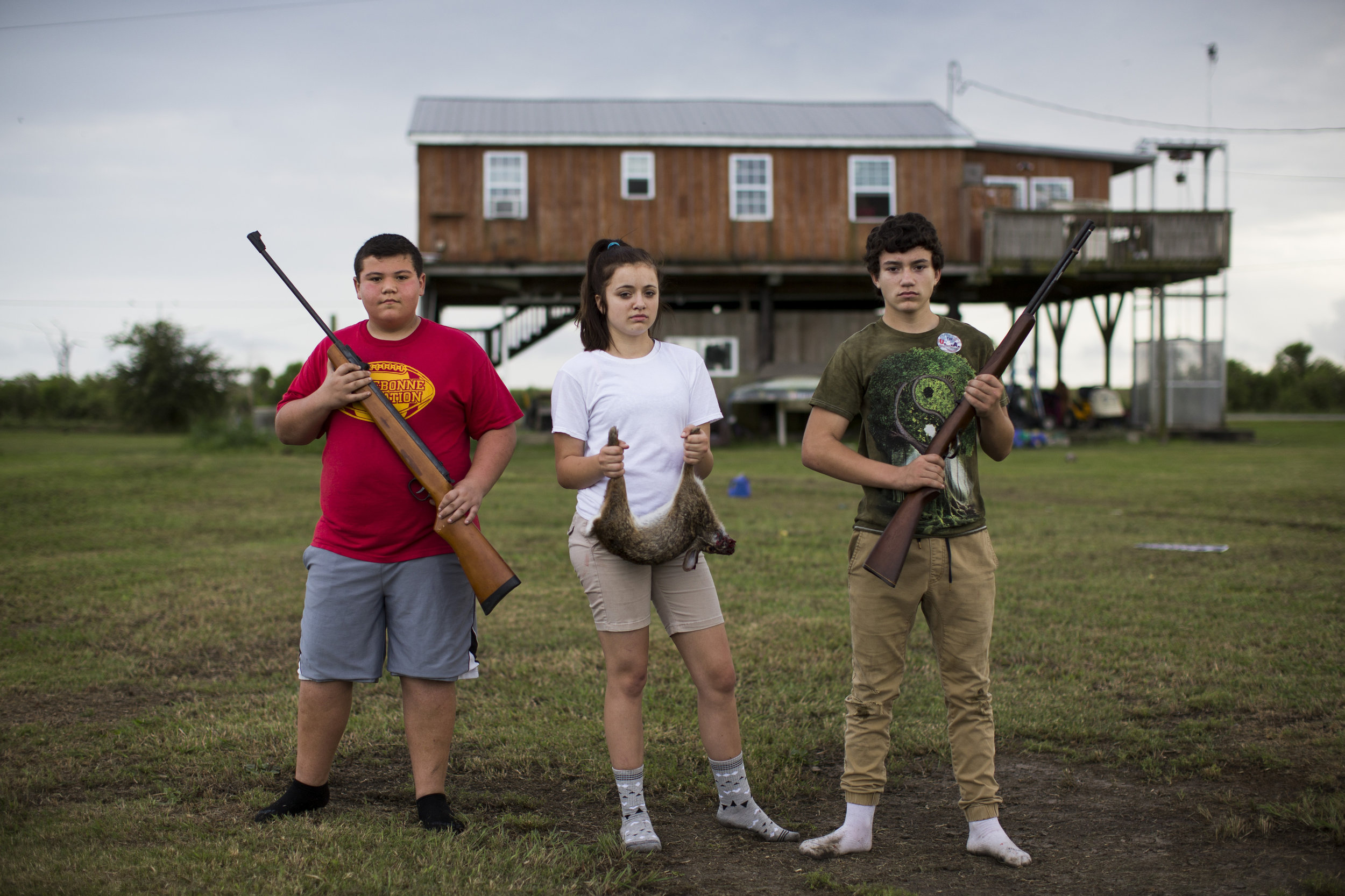 "Reggie Parfait, left, Juliette Brunet, and Howard Brunet stand for a portrait behind their uncle Chris Brunet's house on Isle de Jean Charles, Louisiana, USA on April 21, 2016. ""We have to be careful with the .22; we need those shells for food,"" Chris, who is raising Juliette and Howard, said. Because they do not have a car and Chris is in a wheelchair, they cannot always get off of the island to get groceries. Instead, they make do with the limited resources the island can still provide. On this night, they made rabbit stew. Chris Brunet is the eighth generation in his family to live on the island as a member of the tribe. In one generation, ""this island has gone from being self-sufficient and fertile to relying on grocery stores,"" he says. ""What you see now is a skeleton of the island it once was."" Since 1955, the Isle de Jean Charles Band of Biloxi-Chitimacha-Choctaw Tribe has lost 98 percent of its land to the encroaching Gulf waters. The Tribe's identity, food, and culture have slowly eroded with the land. In response, the Department of Housing and Urban Development awarded the Tribe $48 million to relocate through the National Disaster Resilience Competition. As the effects of climate change transform coastal communities around the world, the people of Isle de Jean Charles will be only 60 of the estimated 200 million people in coastal communities globally who could be displaced by 2050 because of climate change.  This image was a part of  Th  e First Official Climate Refugees in the U.S. Race Against Time  story I wrote and photographed for National Geographic."
