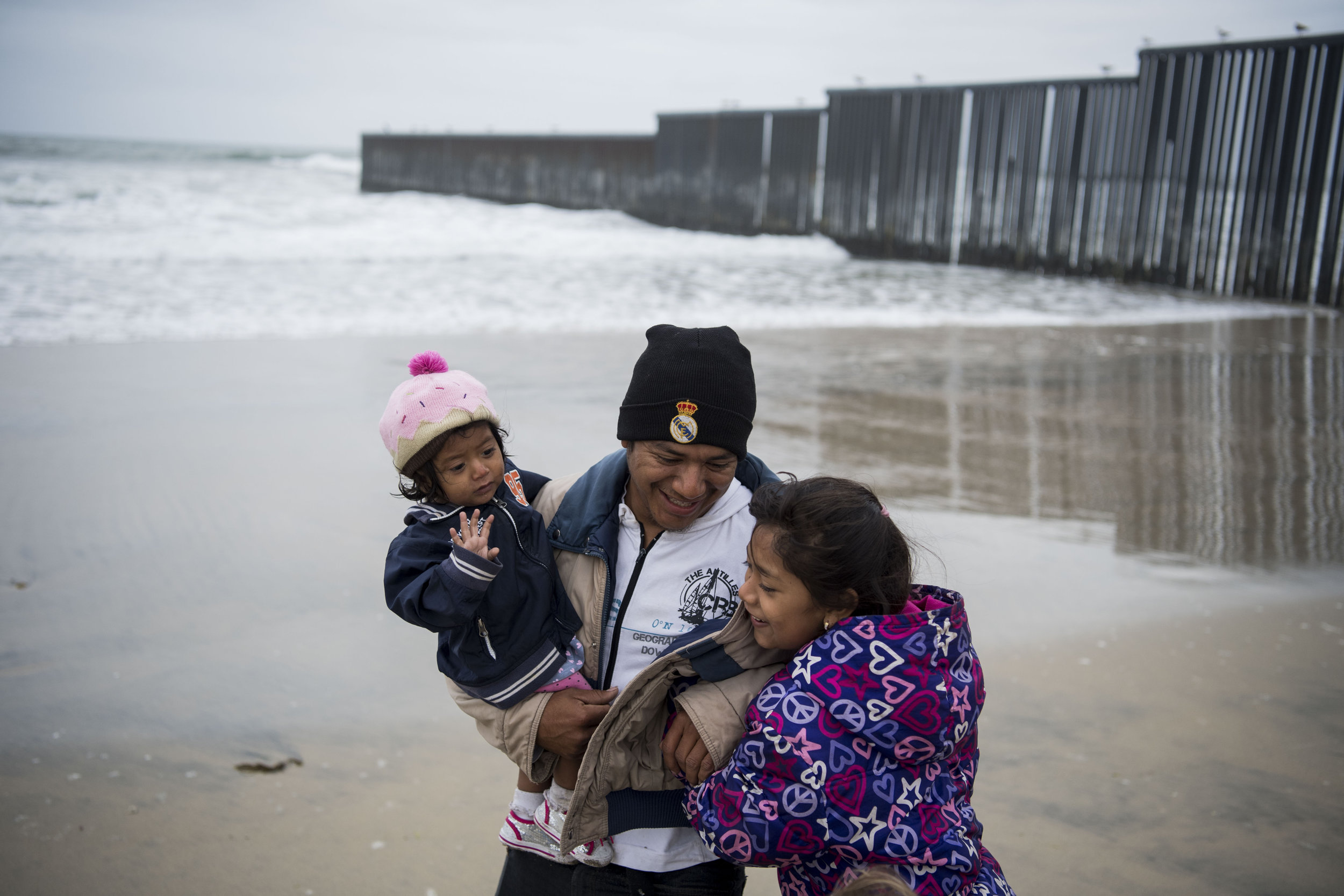 William Rafael Carranza Martinez laughs after running away from the waves with Jessica Carolina Dominguez Martinez, 1, and Elda Hidalia Martinez, 9, near the border wall before marrying his partner at the beginning of the March Without Borders at Friendship Park on April 29, 2018 in Tijuana, Mexico. Hundreds of migrants from Central America traveled for about a month across Mexico to reach the United States border. In the afternoon, the group, including the Martinez family, plans to go to the San Ysidro border crossing south of San Diego, California, where many of the migrants will seek asylum.