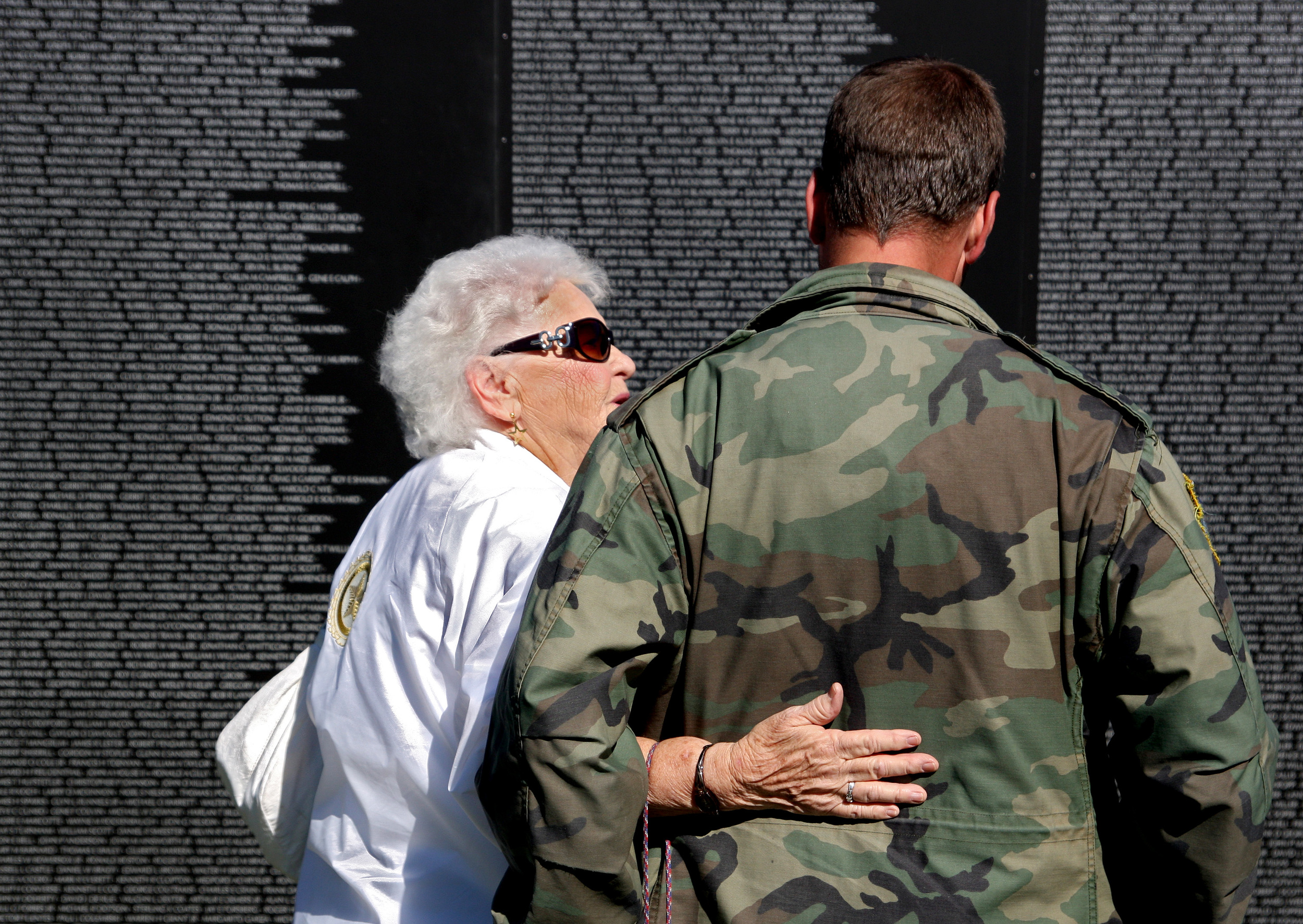 10/16/10 -- Aline Silvia comforts Brian Richardson at the replica Vietnam memorial at the Freedom Tribue in Suffolk.  Silvia's son is listed on the panel in front of them.