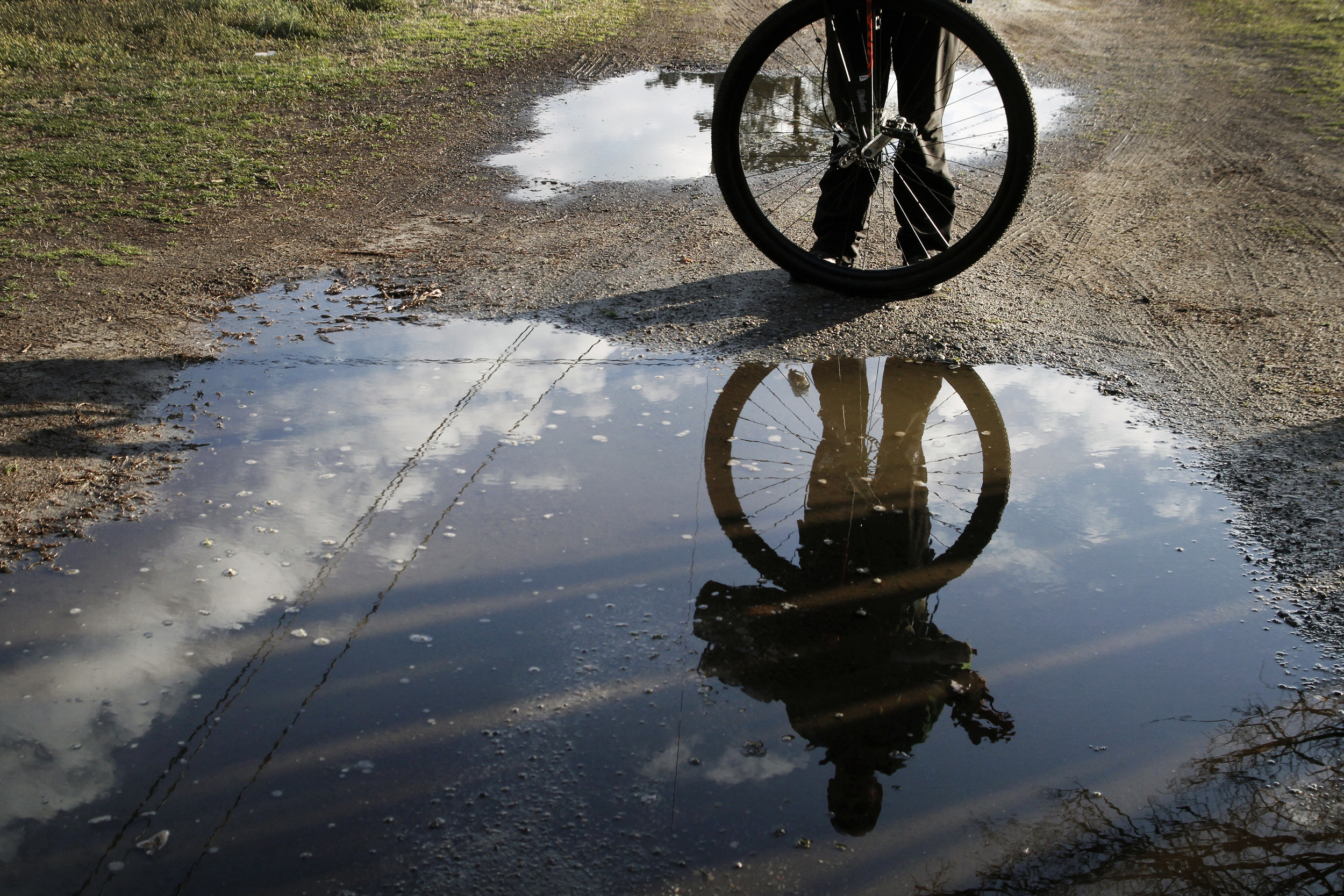 Erickson and his unicycle are reflected in a puddle from the morning's rainstorms as he figures out what to do with his gear for the night.