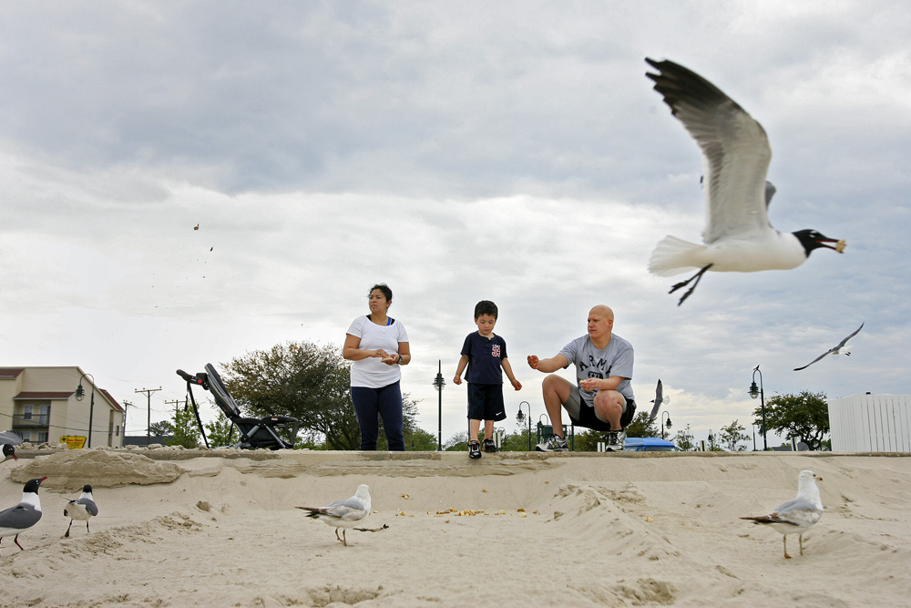 5/8/13 -- Leslie, Noeh and Roel Ramon feed the birds at Buckroe Beach in Hampton.
