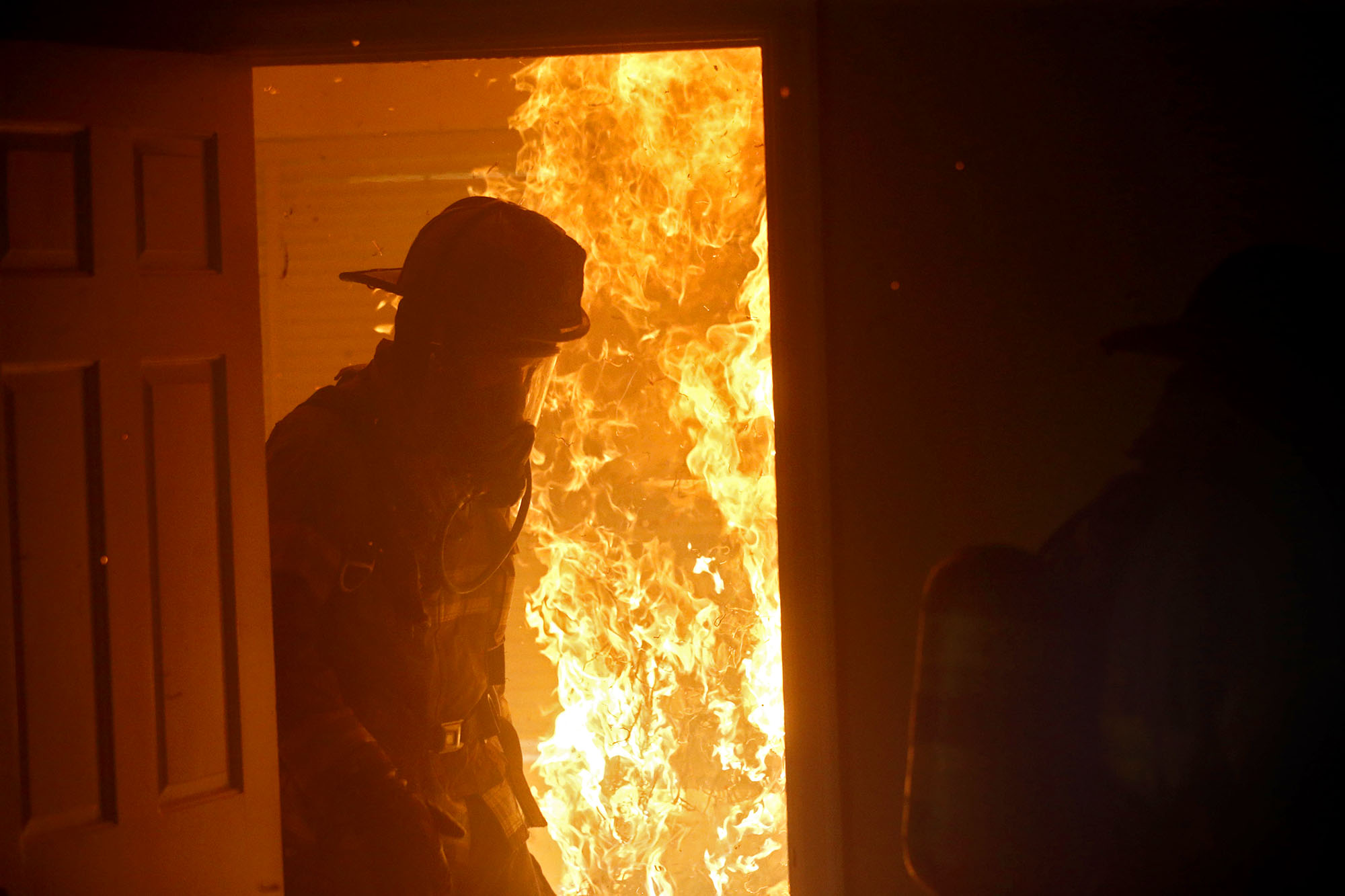"Firefighters emerge from a bedroom after starting a fire during a ""live burn"" exercise on Tuesday, June 28, 2016 in Charlottesville, Va. The house, which is scheduled to be demolished for new construction, provided an opportunity for Albemarle County Fire Rescue to train in a realistic environment, specifically focusing on deployment of hose line."