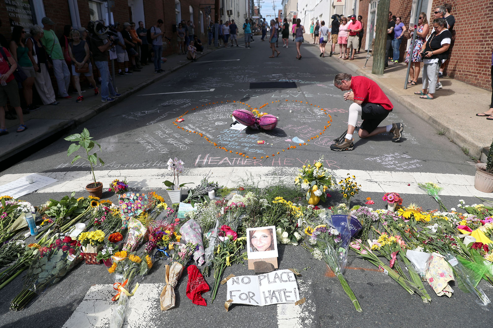 People visit a makeshift memorial for Heather Heyer on 4th Street at the Downtown Mall on Sunday, August 13, 2017. Heyer was killed Saturday when James Alex Fields, Jr. drove a Dodge Challenger into a crowd marching up the street.