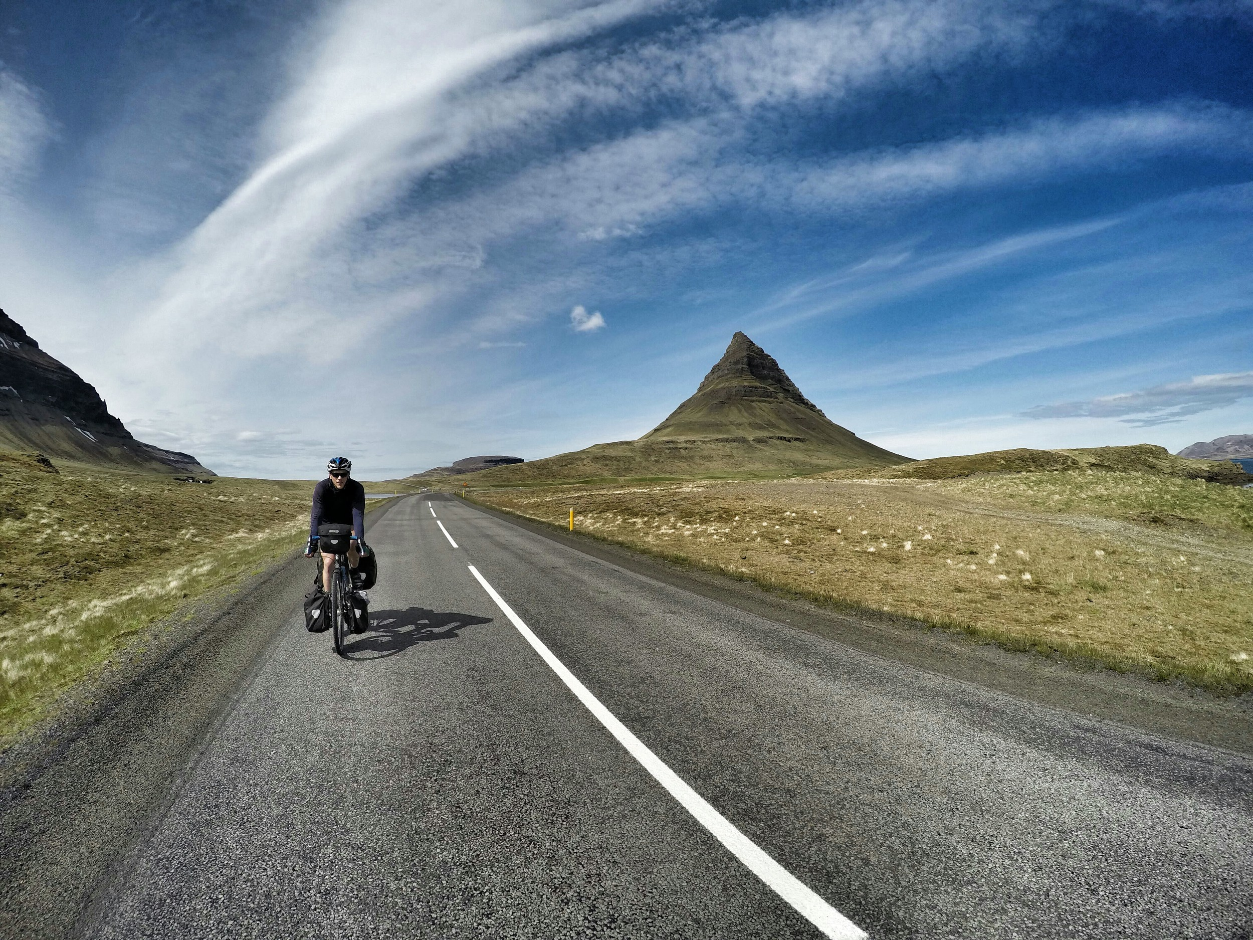 This is Jason riding by the summit of Kirkjufell. We saw this rock feature on many postcards but were slightly unimpressed relative to all the landscapes we'd seen previous. This secret to cycle travelis sometimes hard to describe. We're traveling around five times slower than motorists - we have the luxury of intimately digesting every single landscape. Unlike motorists, we aren't rushing around to see the popular sights. I love cycle travel because it delivers a full range of constant simulation. We felt Iceland's rain, sun, and wind. We smelled it's flowers, geysers, and fish factories, and we heard it's birds, sheep,and silence.