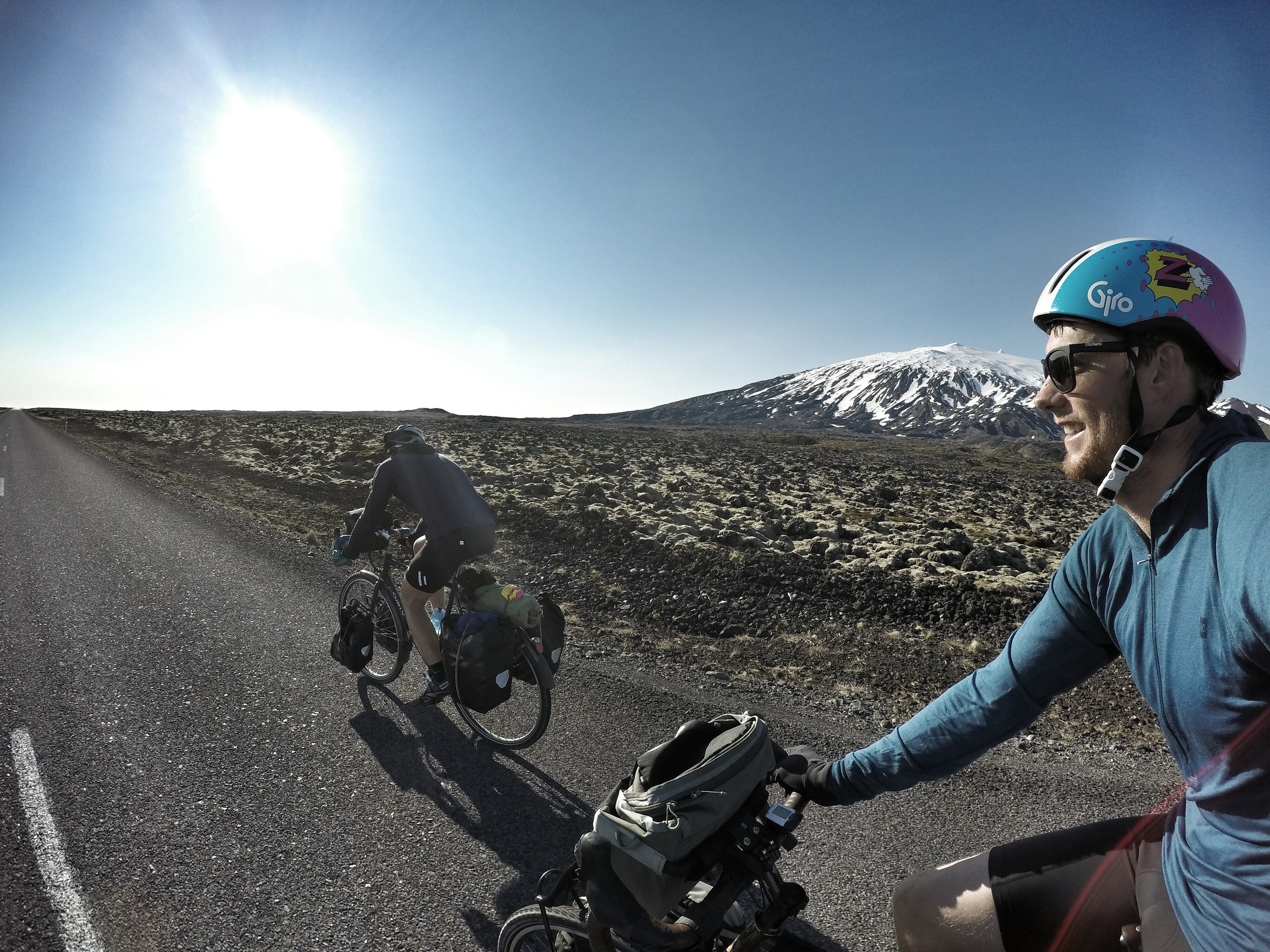 I'm smiling here because of what we just tried to do. Instead of going around the volcano, Snæfellsjökull, shown in background, we tried going over it. We went up the steepest gravel mountain pass road you could dream of with a loaded touring bicycle and on the hottest day of the trip. We started cycling past deep snow on either side of the road, and then pushed our bikes through it. Eventually we got totally denied by kilometers of deep snow over the road. We then had to travel back another 8km to start our 40km windy detour, seen here. Next time I cycle past snowmobilers, I'll take it as a sign of inevitable cycling doom. This volcano is the mountain depicted in Jules Verne's 1864 novel 'Journey to the Centre of the Earth', so if you want to head into the earth, you can find the door somewhere up there.
