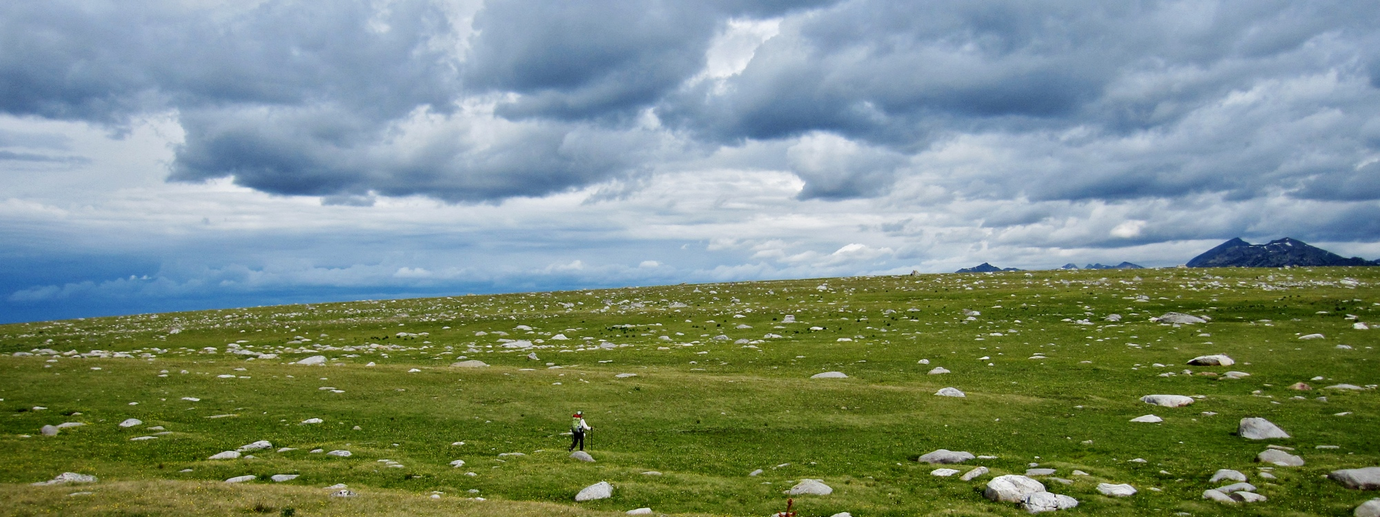 Racing across a plateau with building summer storms. Wind River Range, Wyoming.