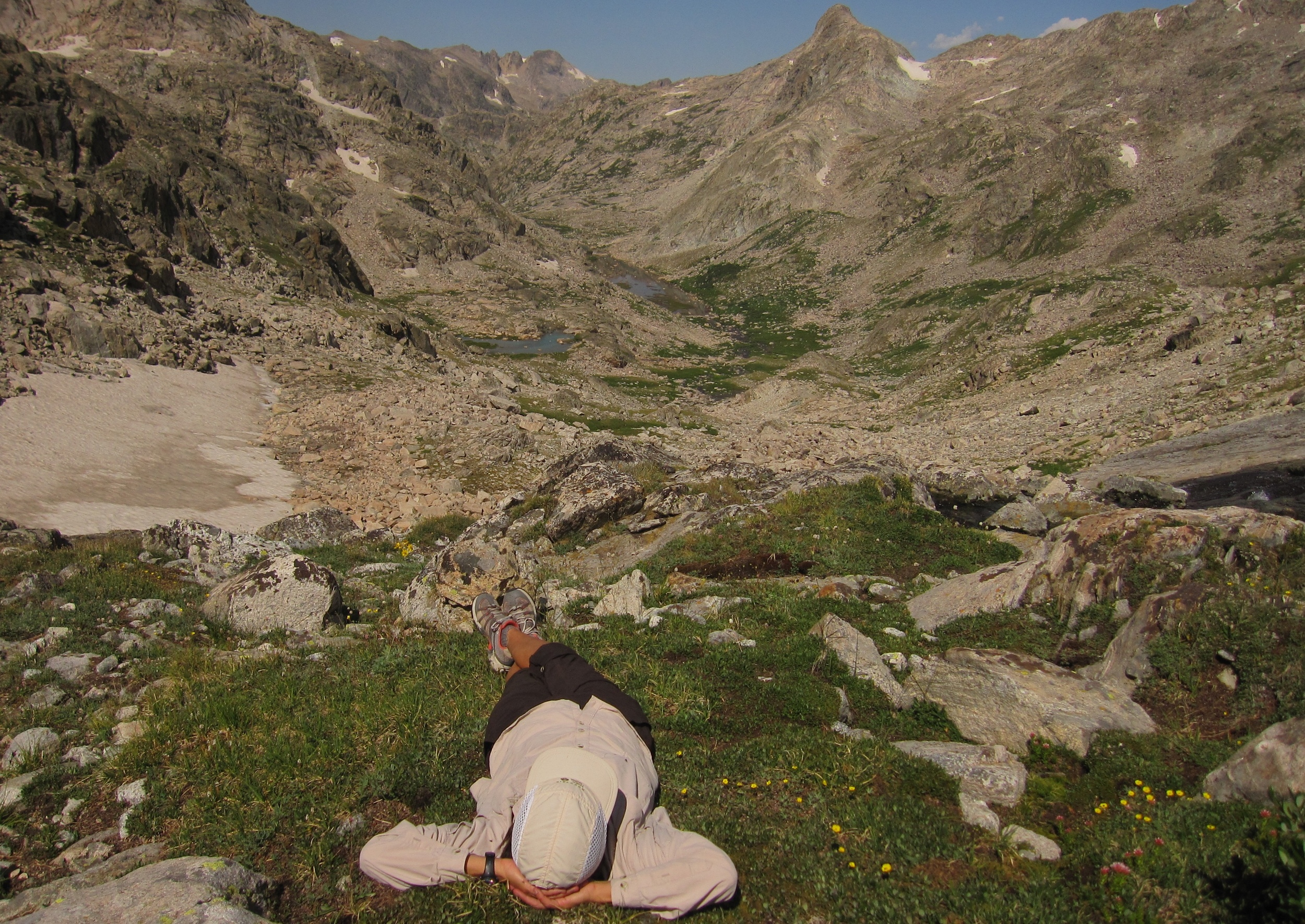 One of the finest lunch spots ever.  A small patch on flat grass on the steep descent from Knapsack Col.  This drainage on the west side of Knapsack Col contains the Stroud Glacier, which is the source of the mighty Green River. The river starts as a small creek below the glacier, then goes down the through the mountains and across the canyonlands of Utah, joins the Colorado River, and flows through the Mojave and Sonoran deserts to the Gulf of California in northern Mexico.