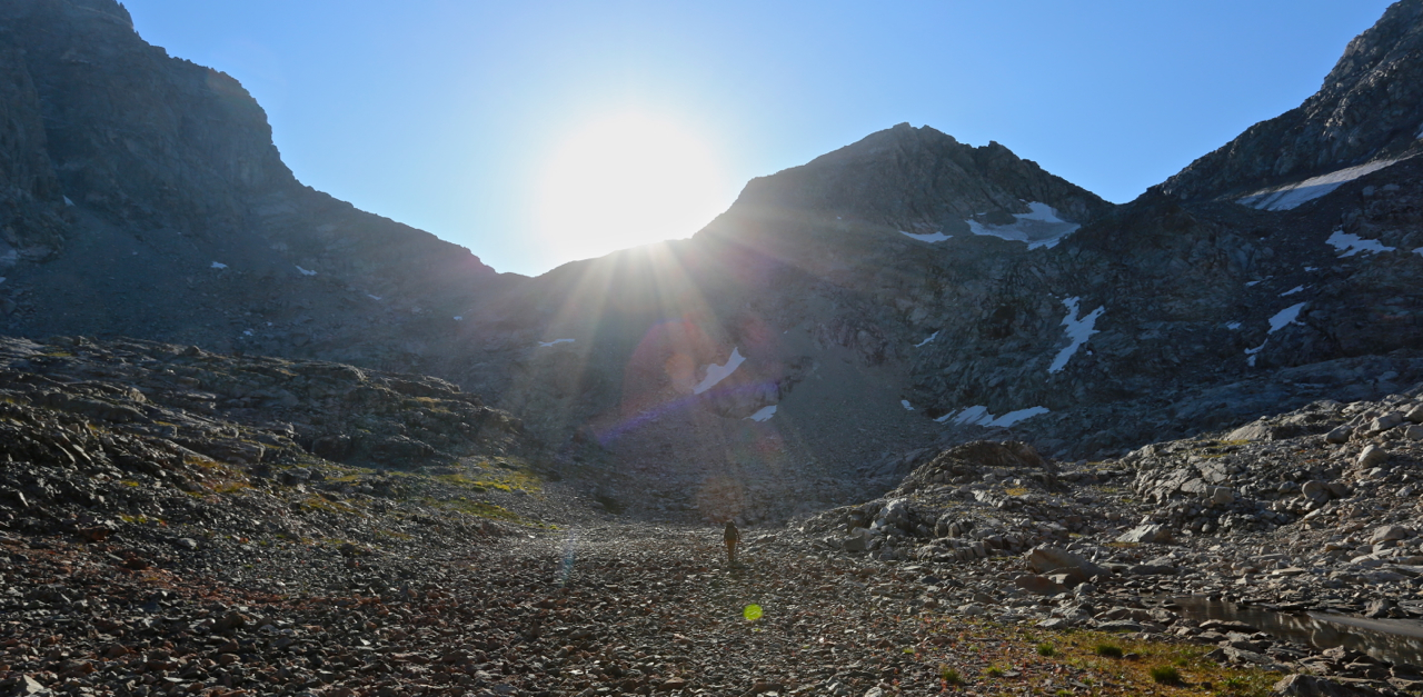 Alan Dixon approaching Knapsack Col, hiking into the early morning sun. This small valley is notable for being the source of the mighty Green River, which originates in the melting snow of the Stroud Glacier - just right of the boundary of this photo.