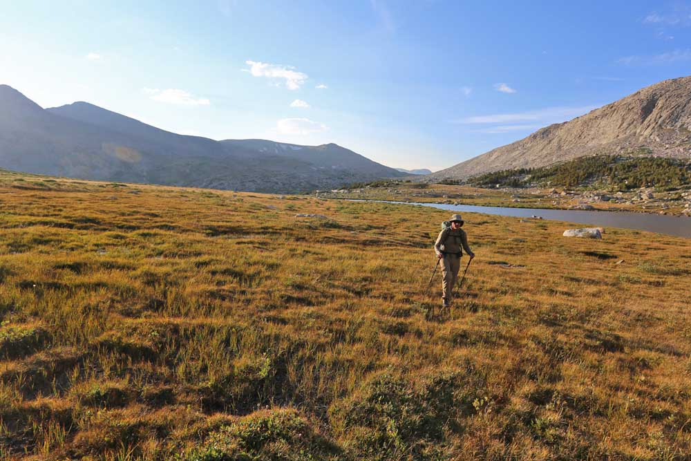 Hiking toward Lake 10555 near sunset, with Hay Pass and the Continental Divide in the background.