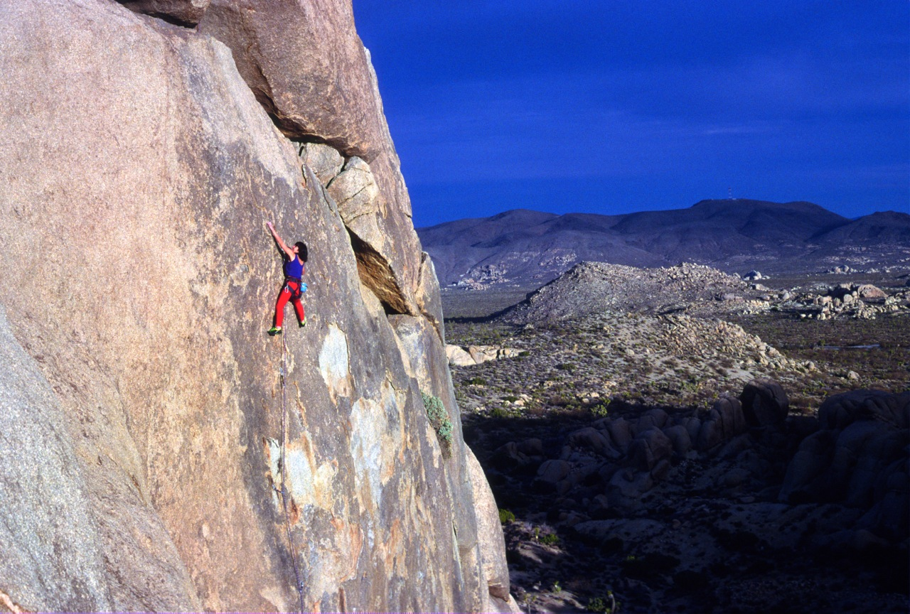 Karen on the second ascent of a beautiful new route we climbed in Joshua Tree National Park almost twenty years ago. This beautiful, sunny wall stays warm all winter and was untouched by climbers when we first came upon it in the early 90s. Solar Oven, 5.10c.