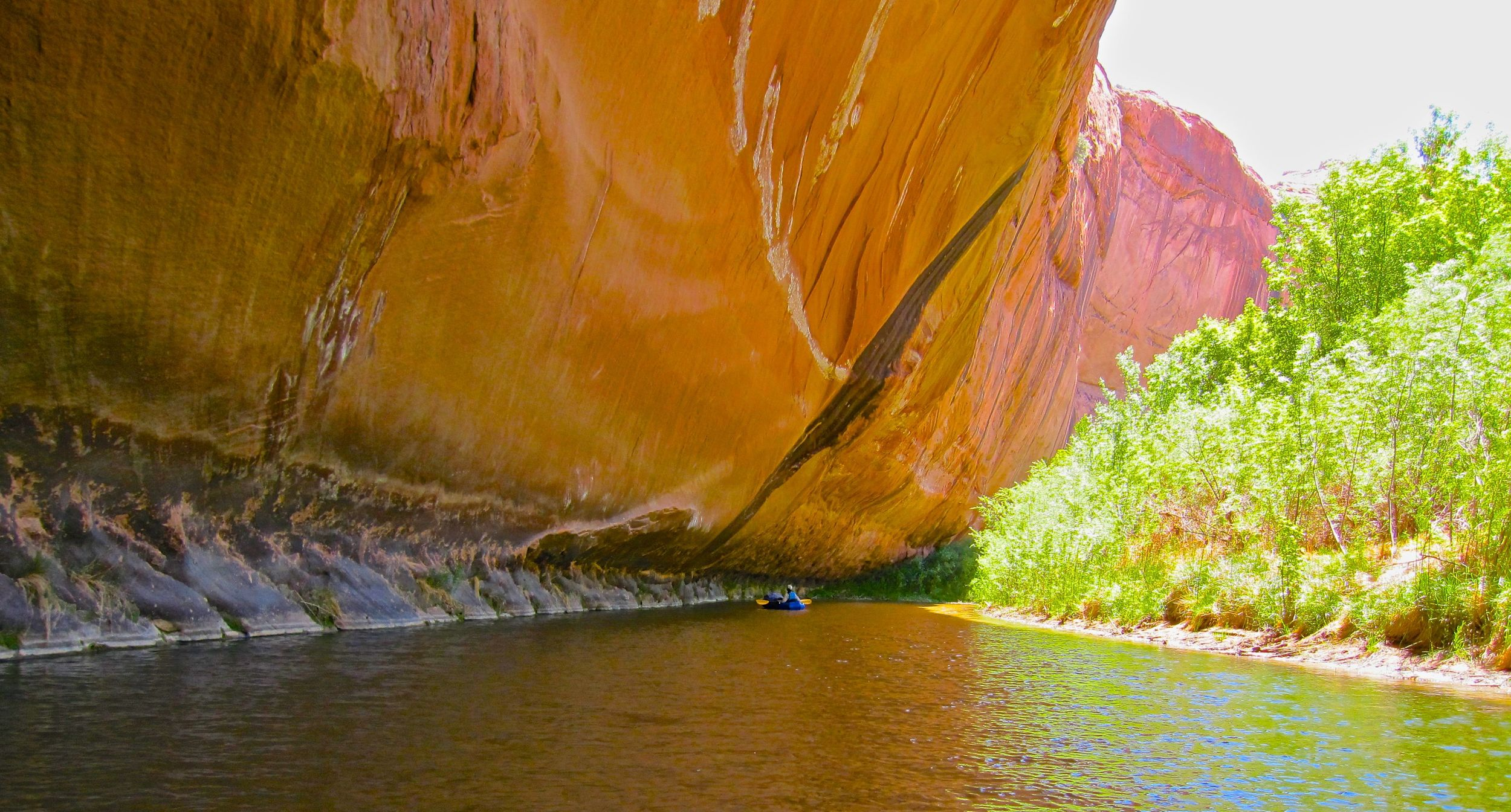 Karen paddles beneath a long alcove that overhangs the river. The key to packrafting in Escalante is heading out while the flow is enough for a good trip. Much of the year the water is too low for paddling along the upper reaches of the river.