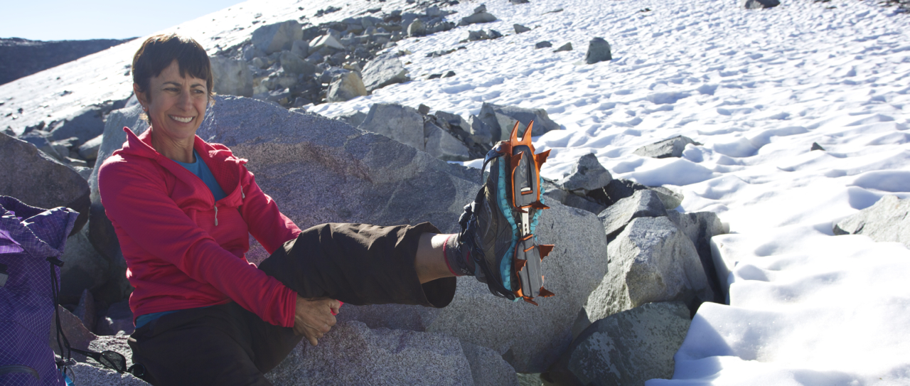 Karen dons her Black Diamond Neve crampons. These are perfect for speedy alpine ascents on moderate ice and snow. They are light (aluminum) and attach easily to trail running shoes or lightweight boots.