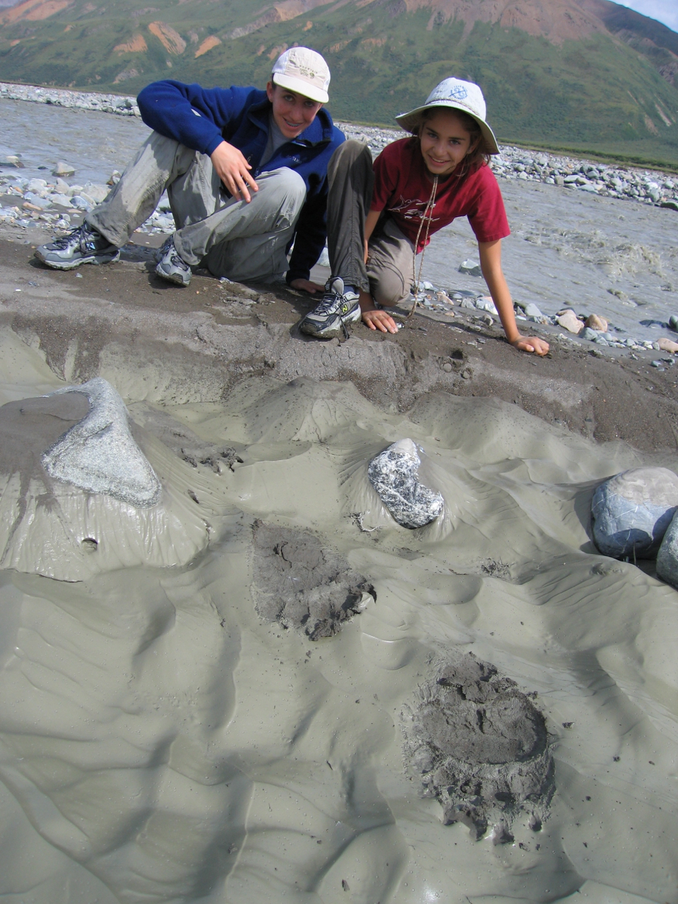 Megan and Amy pose by Grizzly Bear tracks along the Toklat River, Denali National Park. We saw three separate Grizzlies that morning along the river - including the giant one that left these prints before heading onto a slope to munch on blueberries.